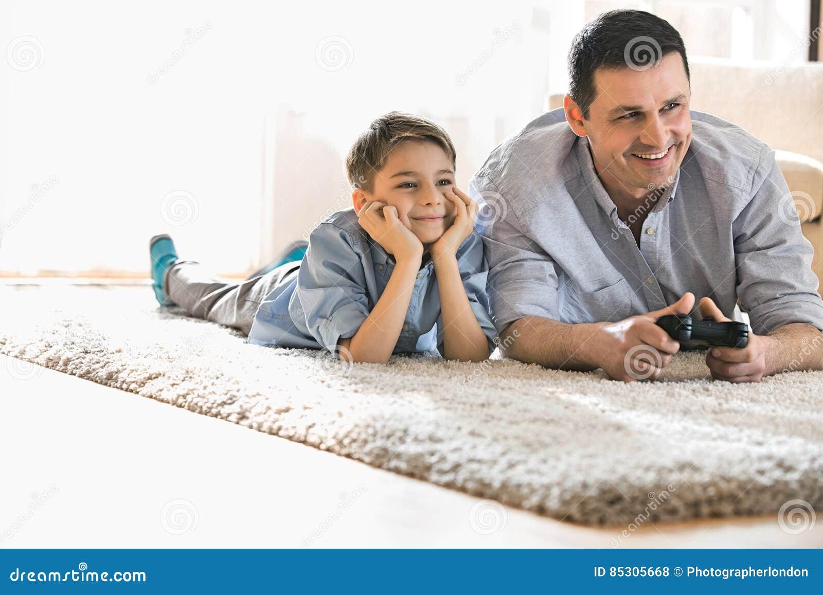 Lycklig fader och son som hemma spelar videospelet på golv
