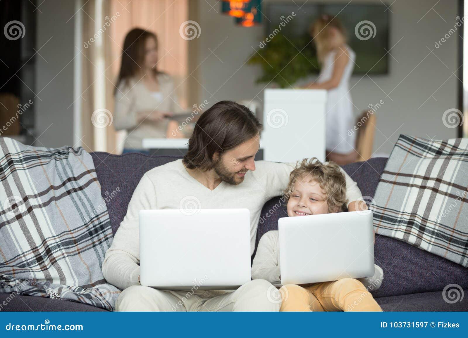 Lycklig fader och son som omfamnar genom att använda bärbara datorer tillsammans hemma