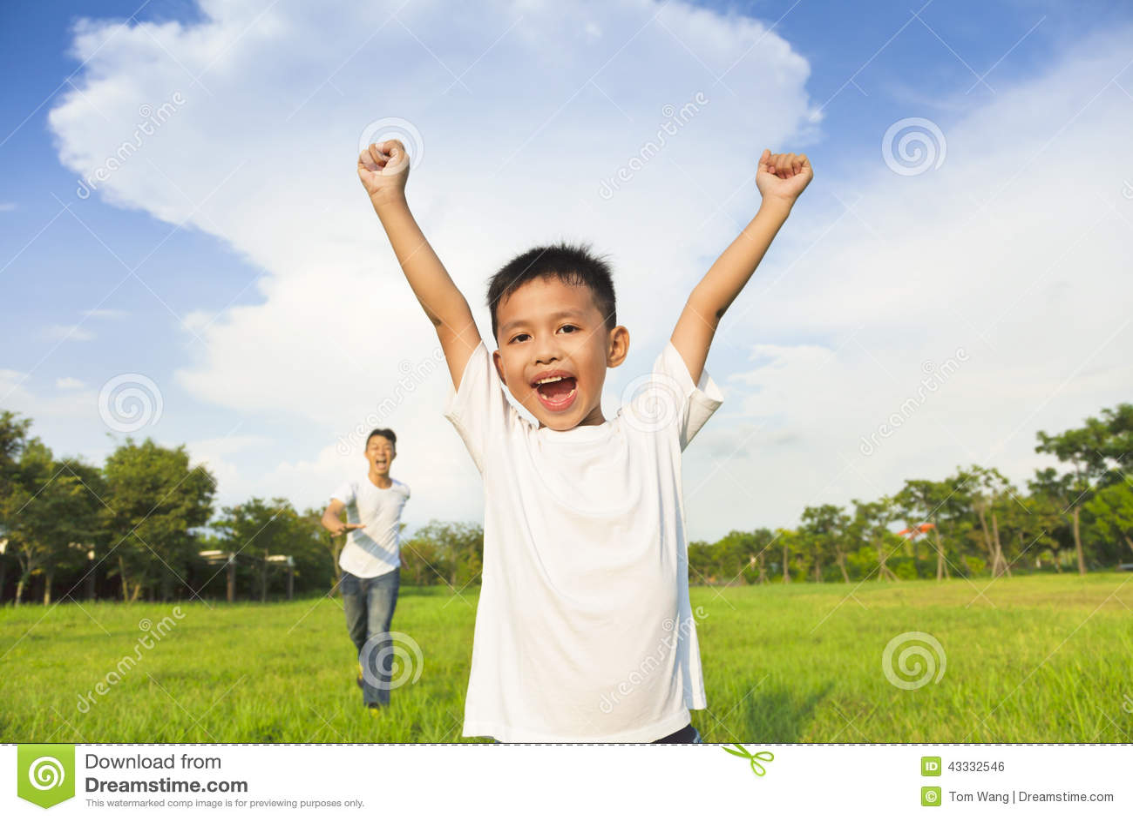 Lycklig fader och son som spelar i äng
