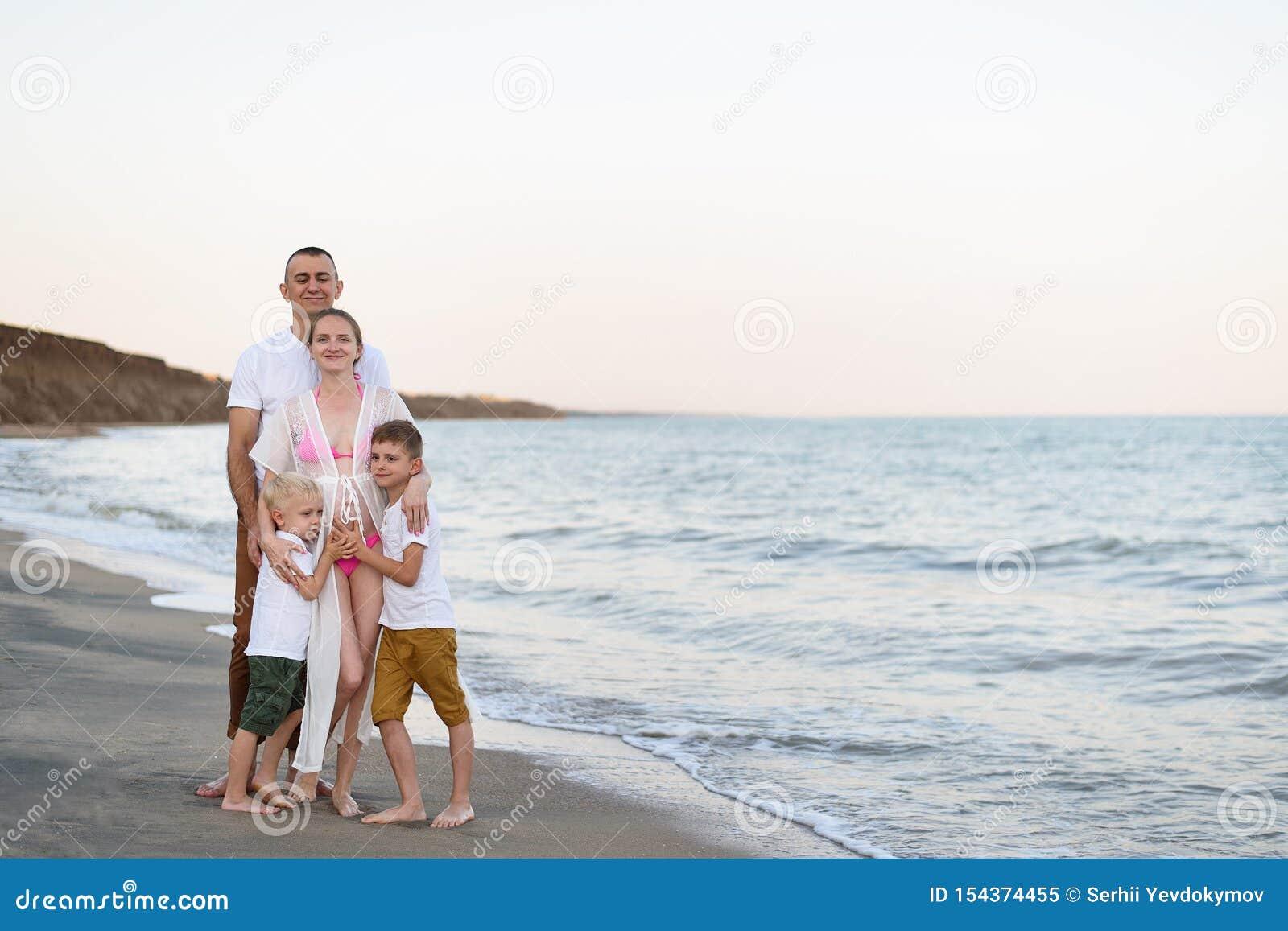 Lycklig familj av fyra som kramar på föräldrarna för havskust, den gravida modern och två söner