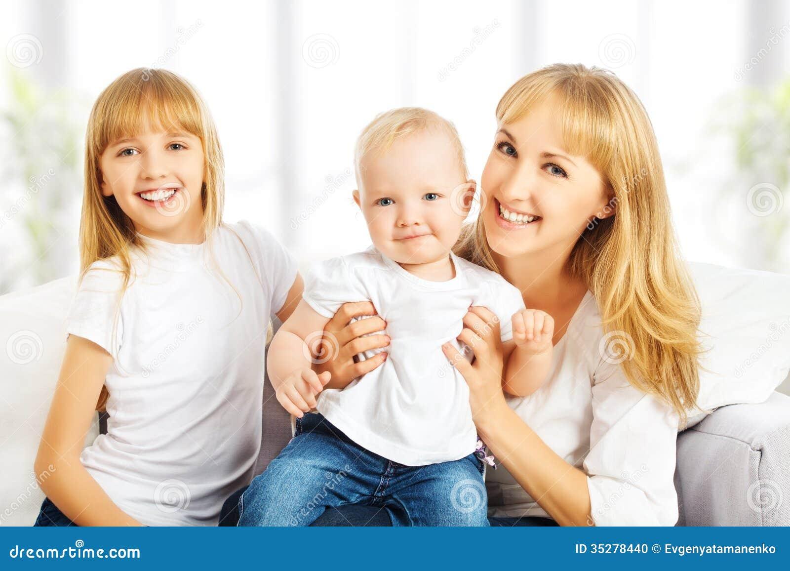 Lycklig familj hemma på soffan. Moder och dotter och son