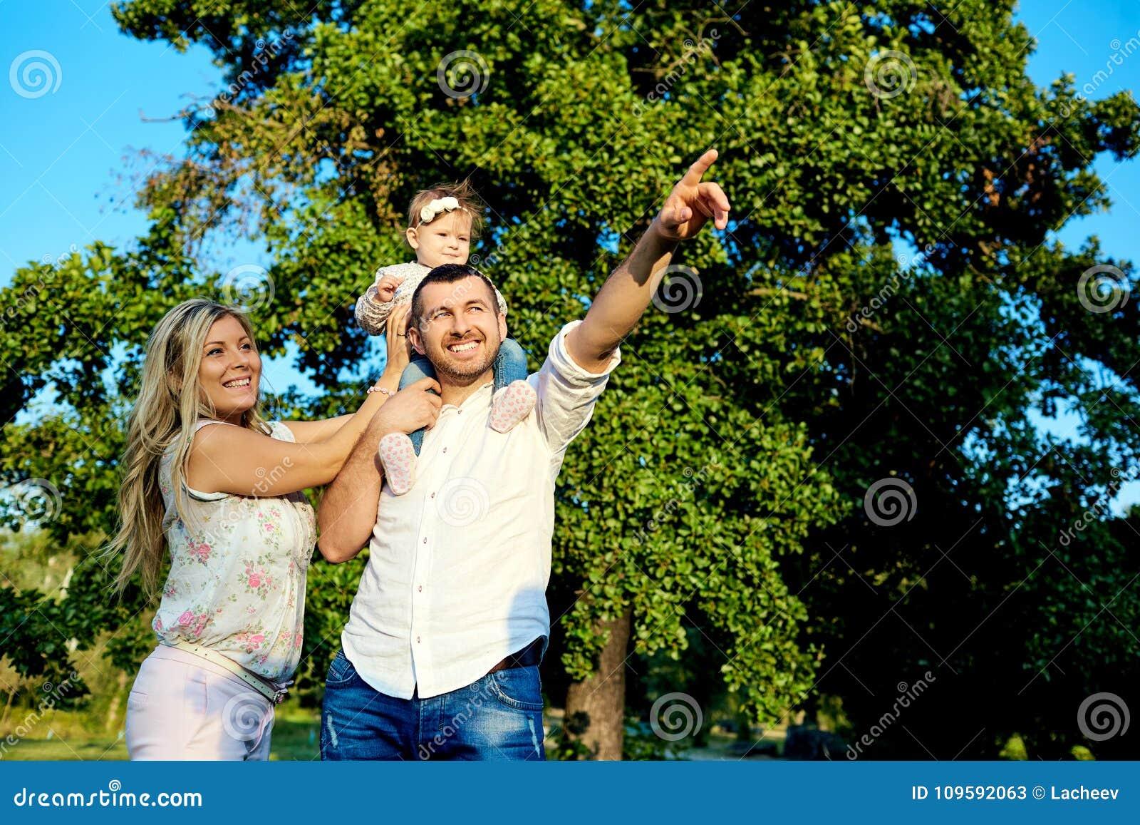Lycklig familj i en parkera i sommarhöst