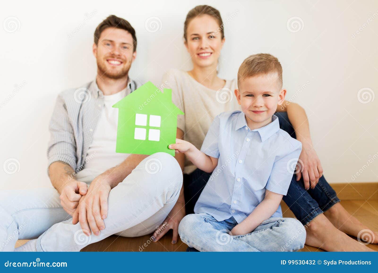 Lycklig familj med det gröna huset som flyttar sig till det nya hemmet