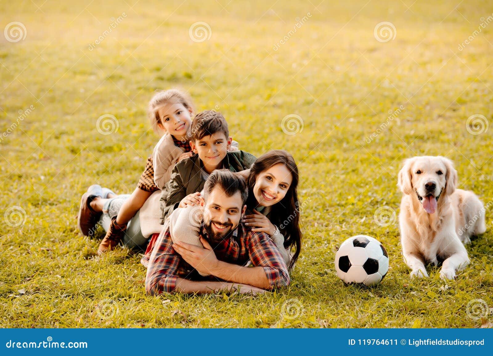 Lycklig familj med två barn som ligger i en hög på gräs med hundsammanträde