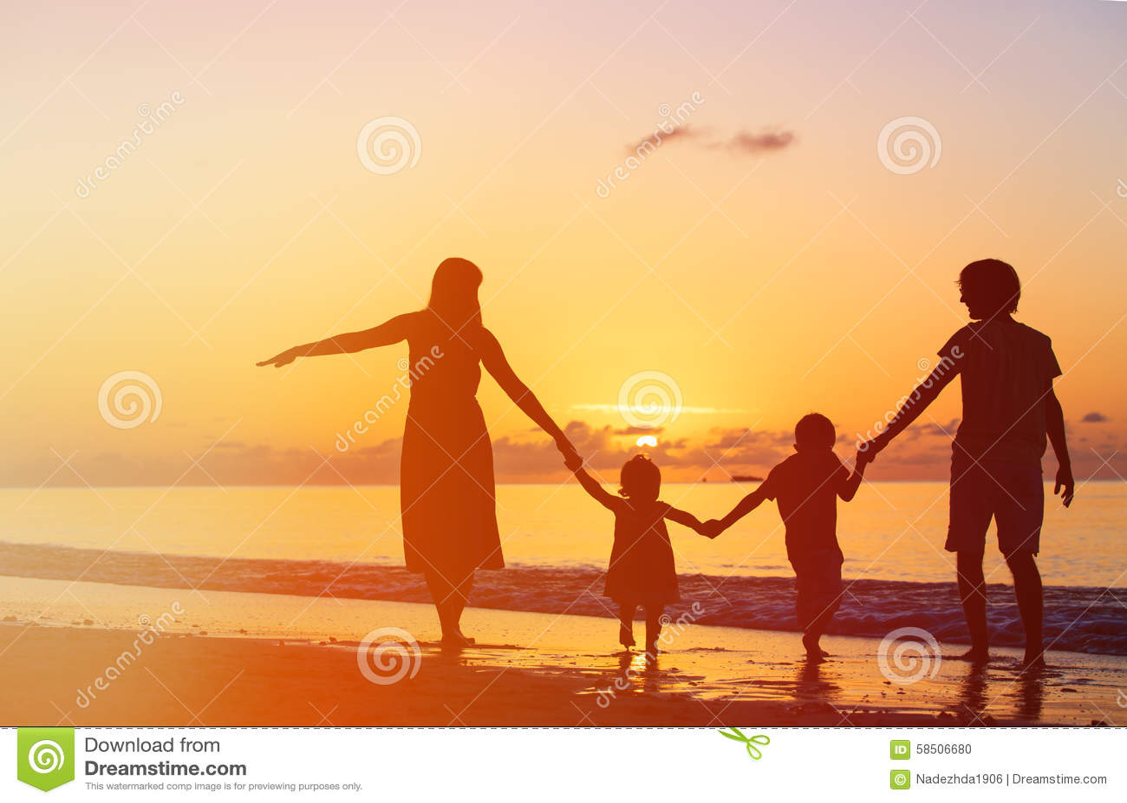Lycklig familj med två ungar som har gyckel på solnedgången