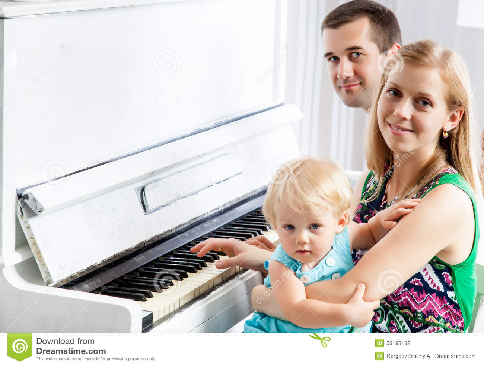 Lycklig familj nära pianot