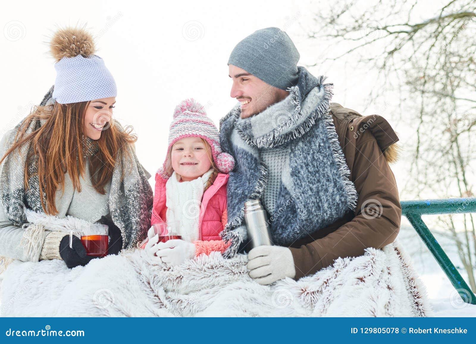 Lycklig familj som dricker te under vintertur