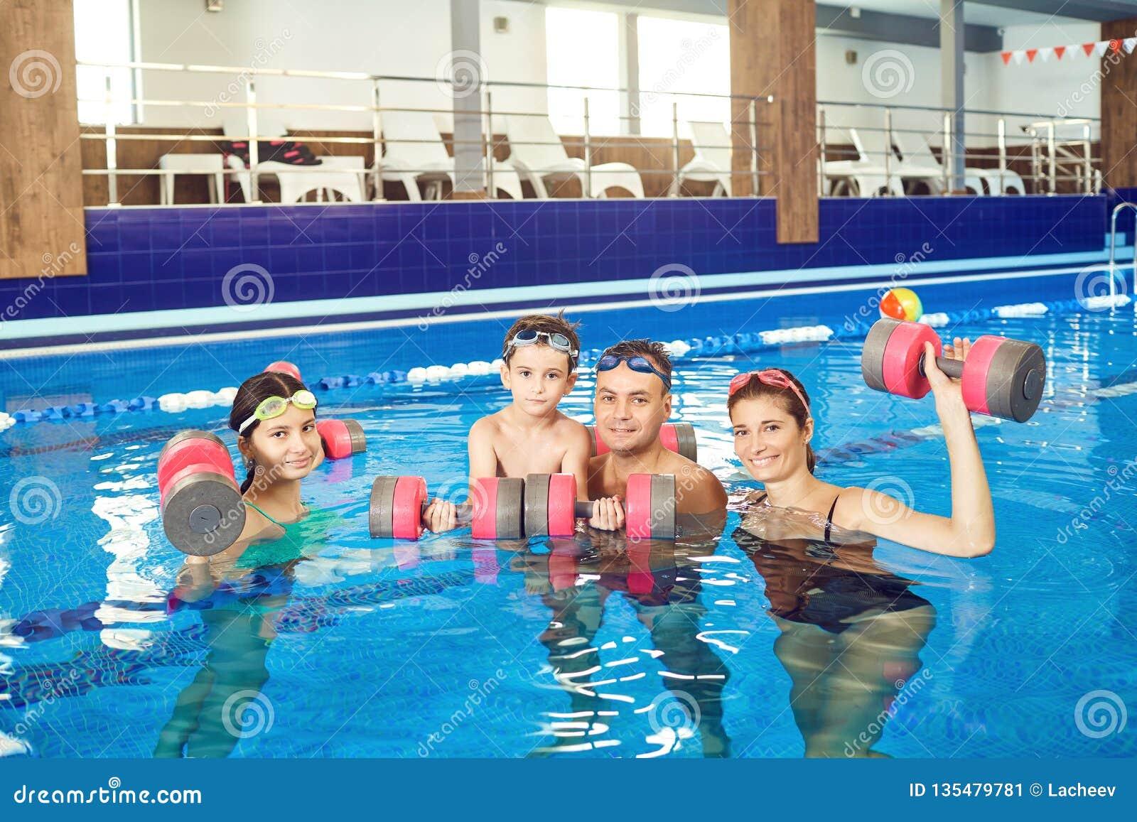 Lycklig familj som gör övningar med hantlar i en simbassäng
