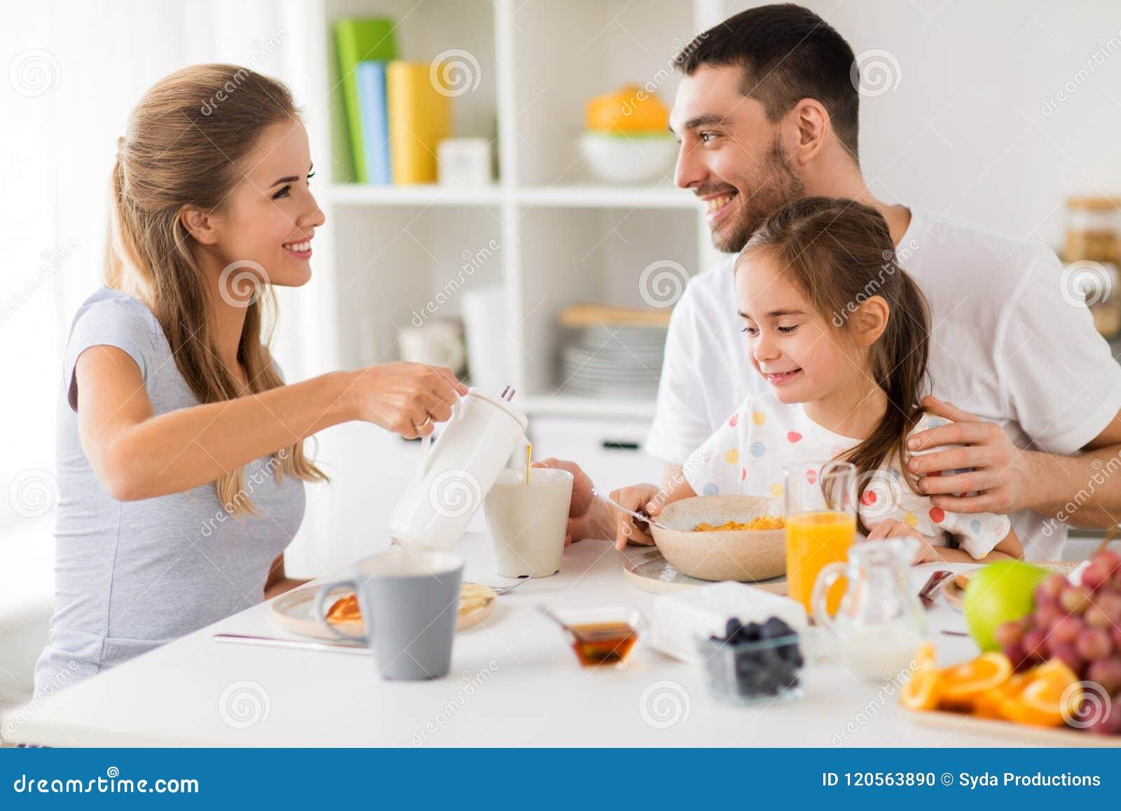 Lycklig familj som har frukosten hemma