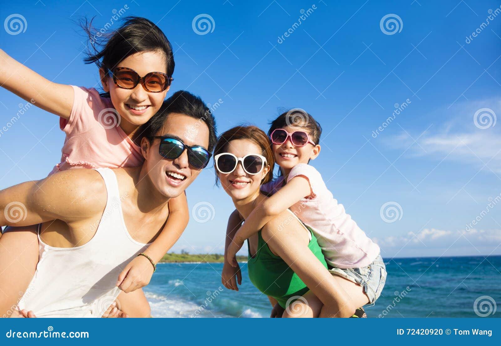 Lycklig familj som har gyckel på stranden