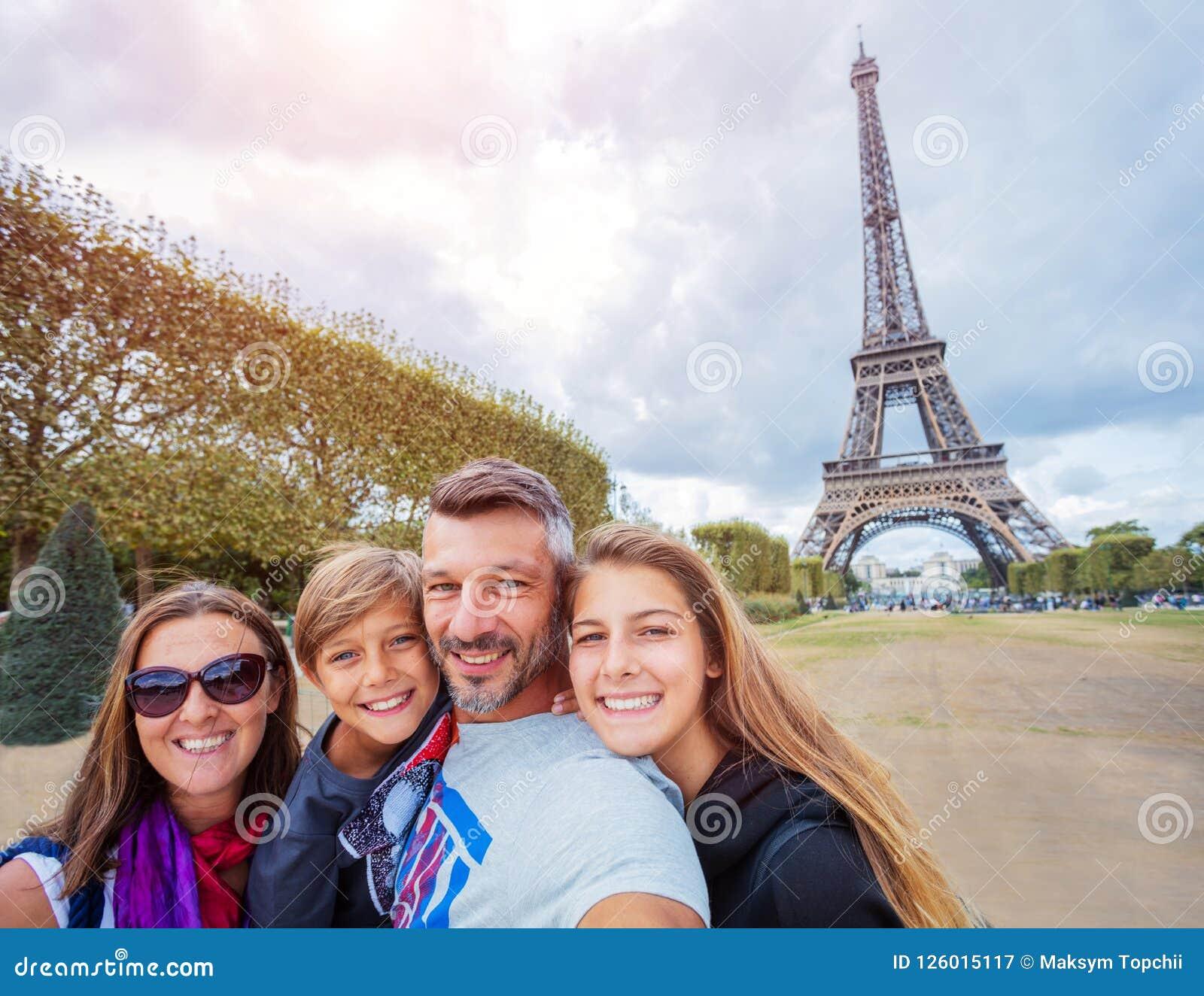 Lycklig familj som har gyckel tillsammans i Paris nära Eiffeltorn