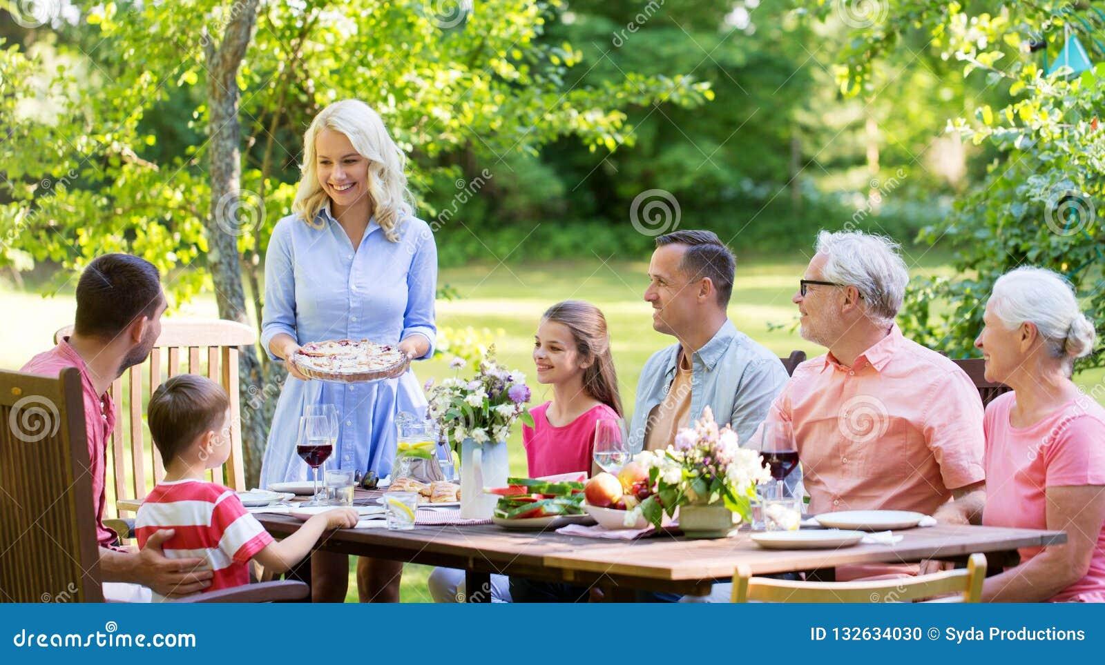 Lycklig familj som har matställen eller det trädgårds- partiet för sommar