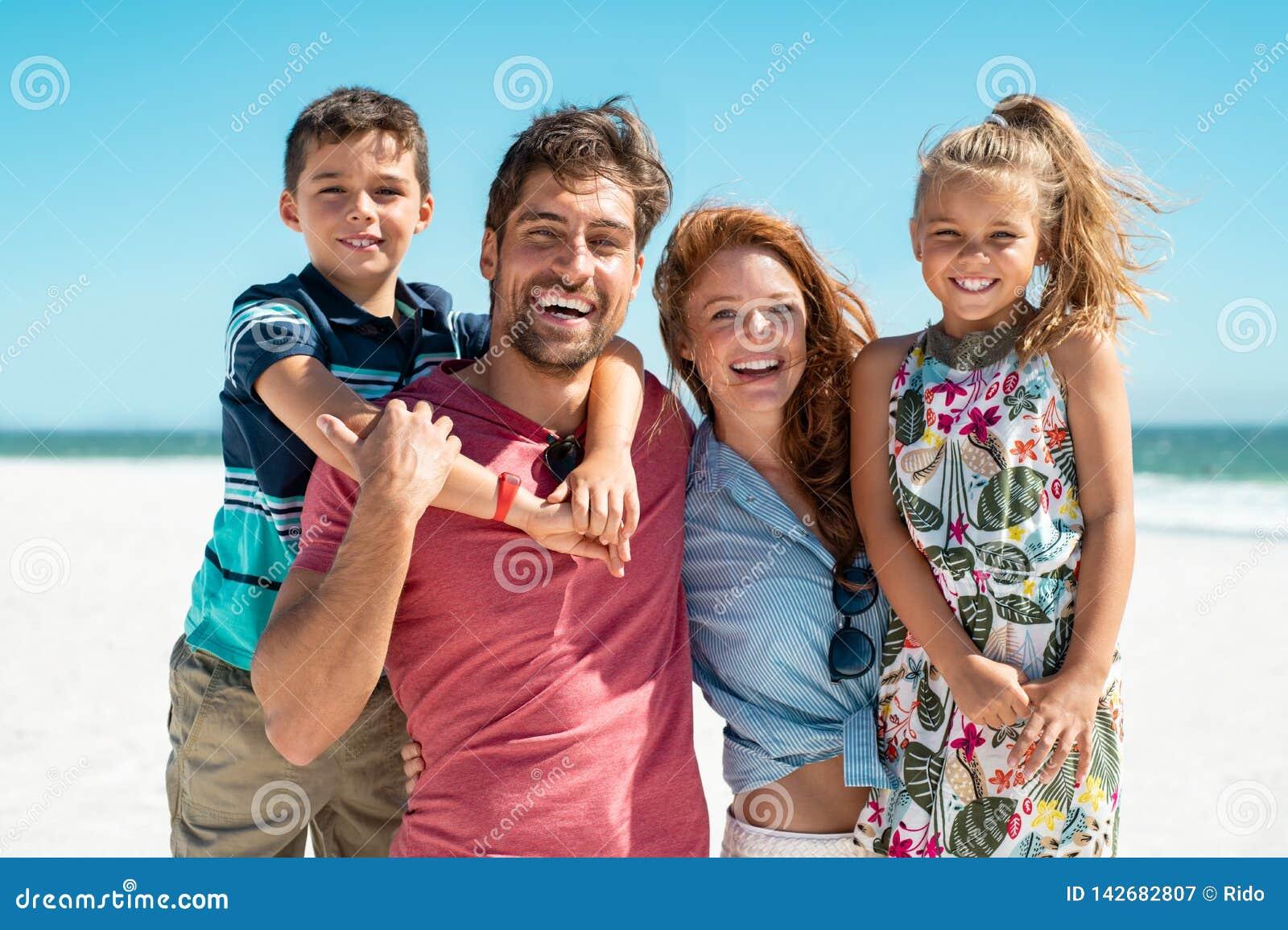 Lycklig familj som ler på stranden