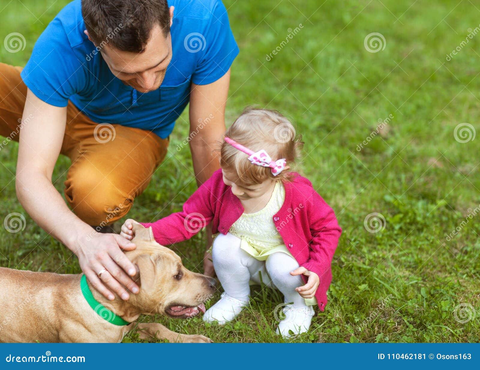 Lycklig familj som spelar i parkera med hans hund