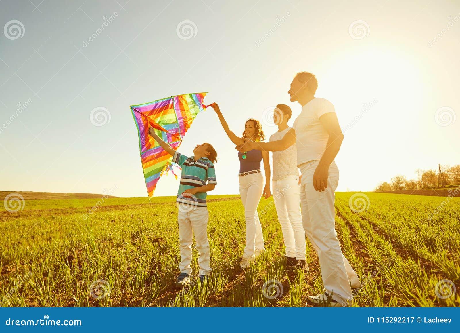 Lycklig familj som spelar med en drake på naturen i våren, sommar