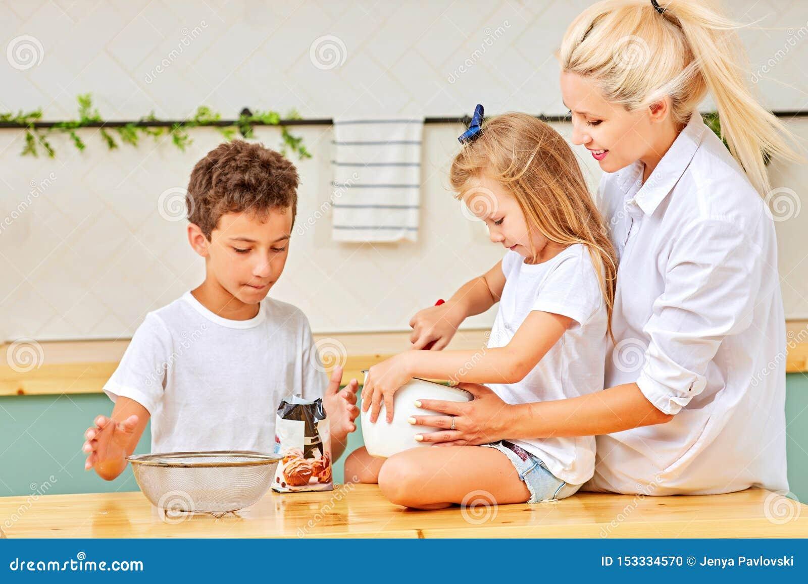 Lycklig familj som tillsammans förbereder bakelse i kök