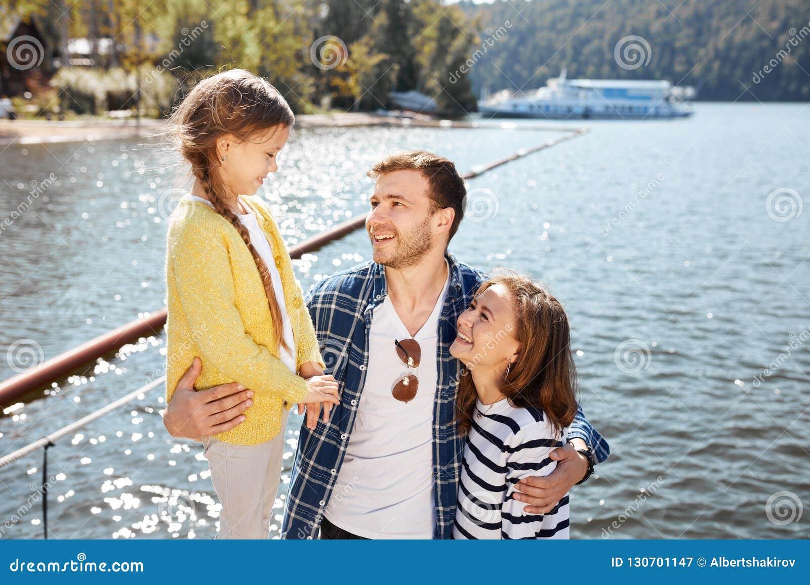 Lycklig familj som tillsammans spenderar tid utanför nära sjön Föräldrar som spelar med dottern som kramar och har gyckel