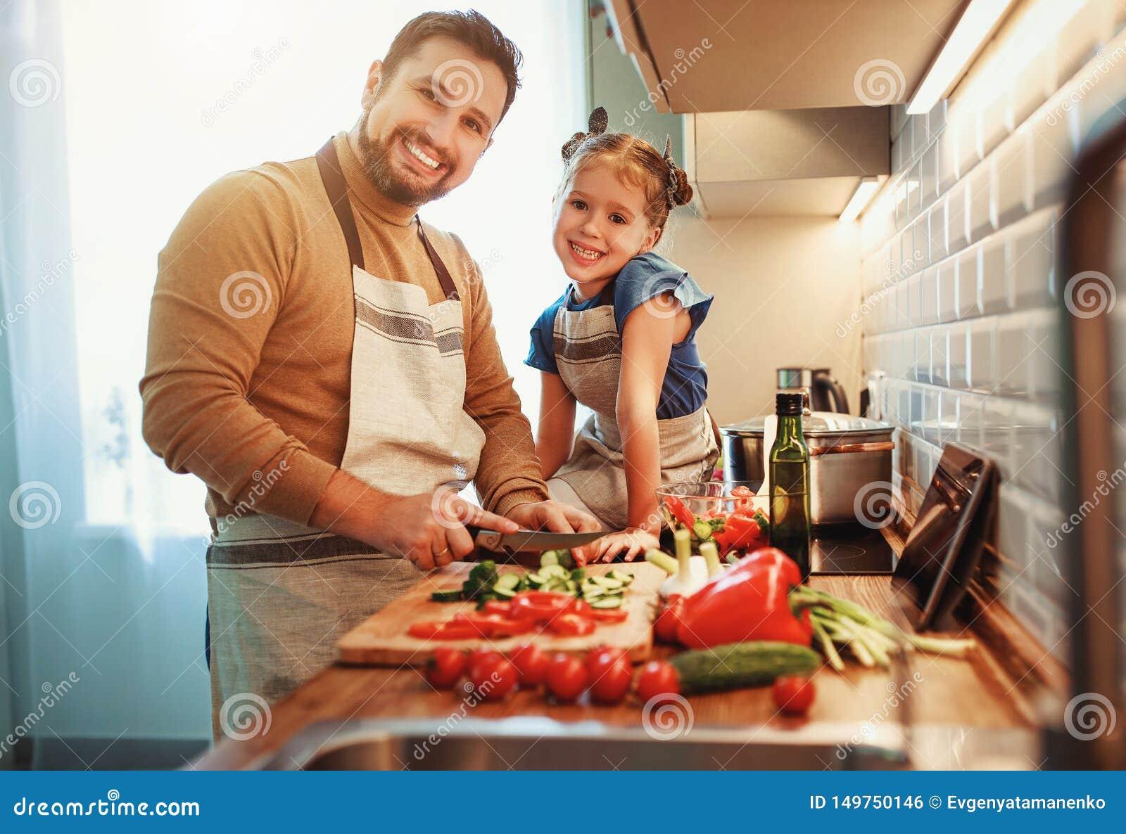 Lycklig familjfader med barndottern som förbereder grönsaksallad