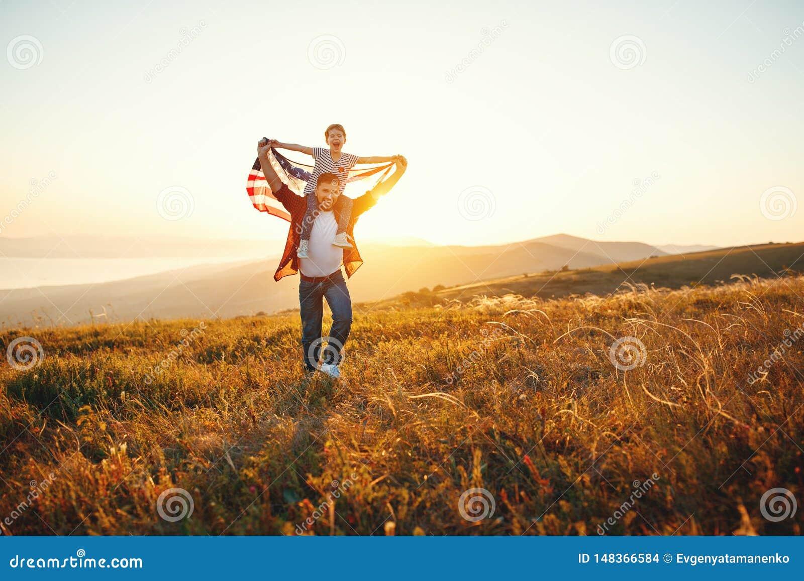 Lycklig familjfader och barn med flaggan av F?renta staterna som tycker om solnedg?ng p? naturen