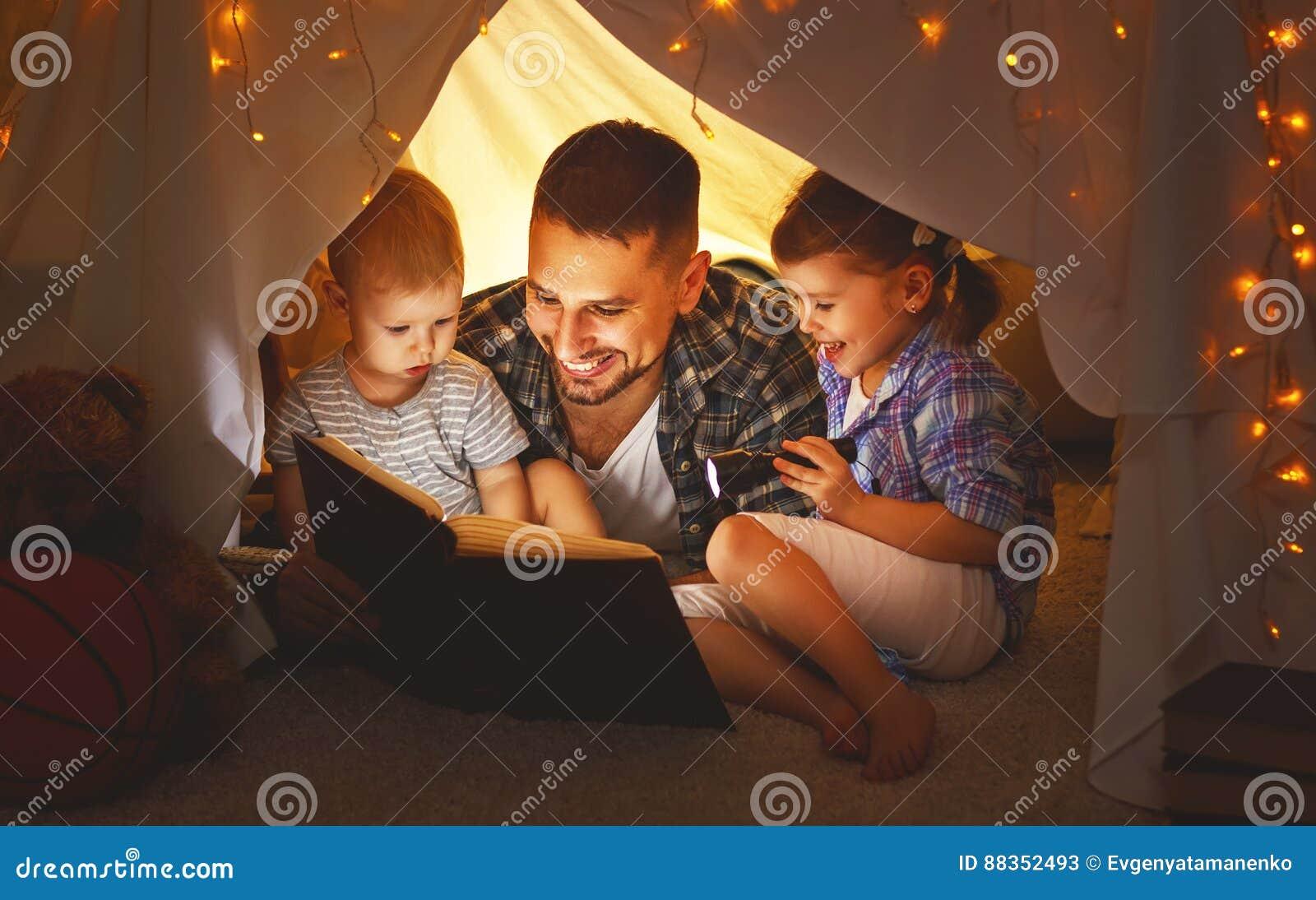 Lycklig familjfader och barn som läser en bok i tält på hom