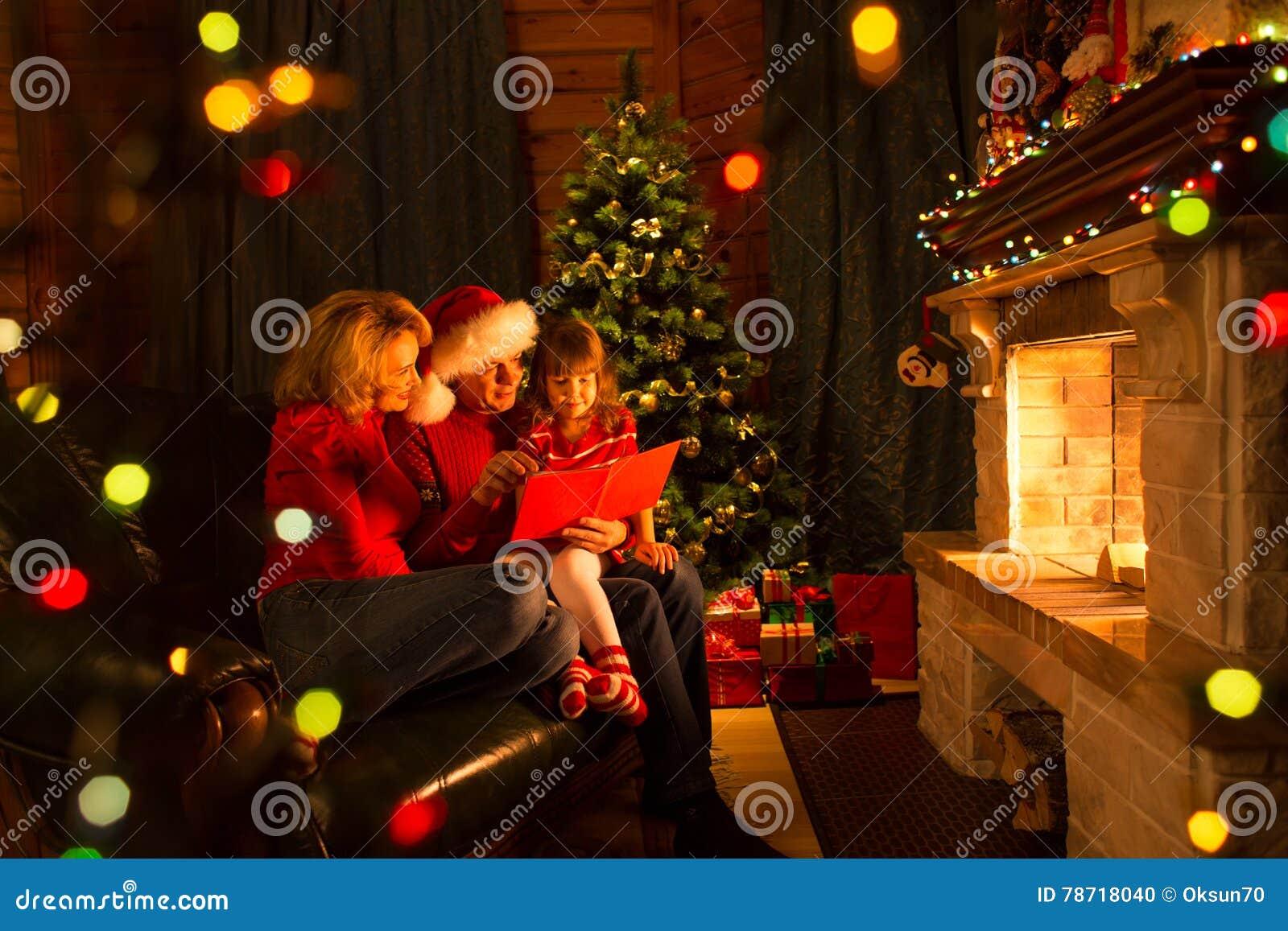 Lycklig familjläsebok hemma vid spisen i varm och hemtrevlig vardagsrum på christmastime för vinterdag