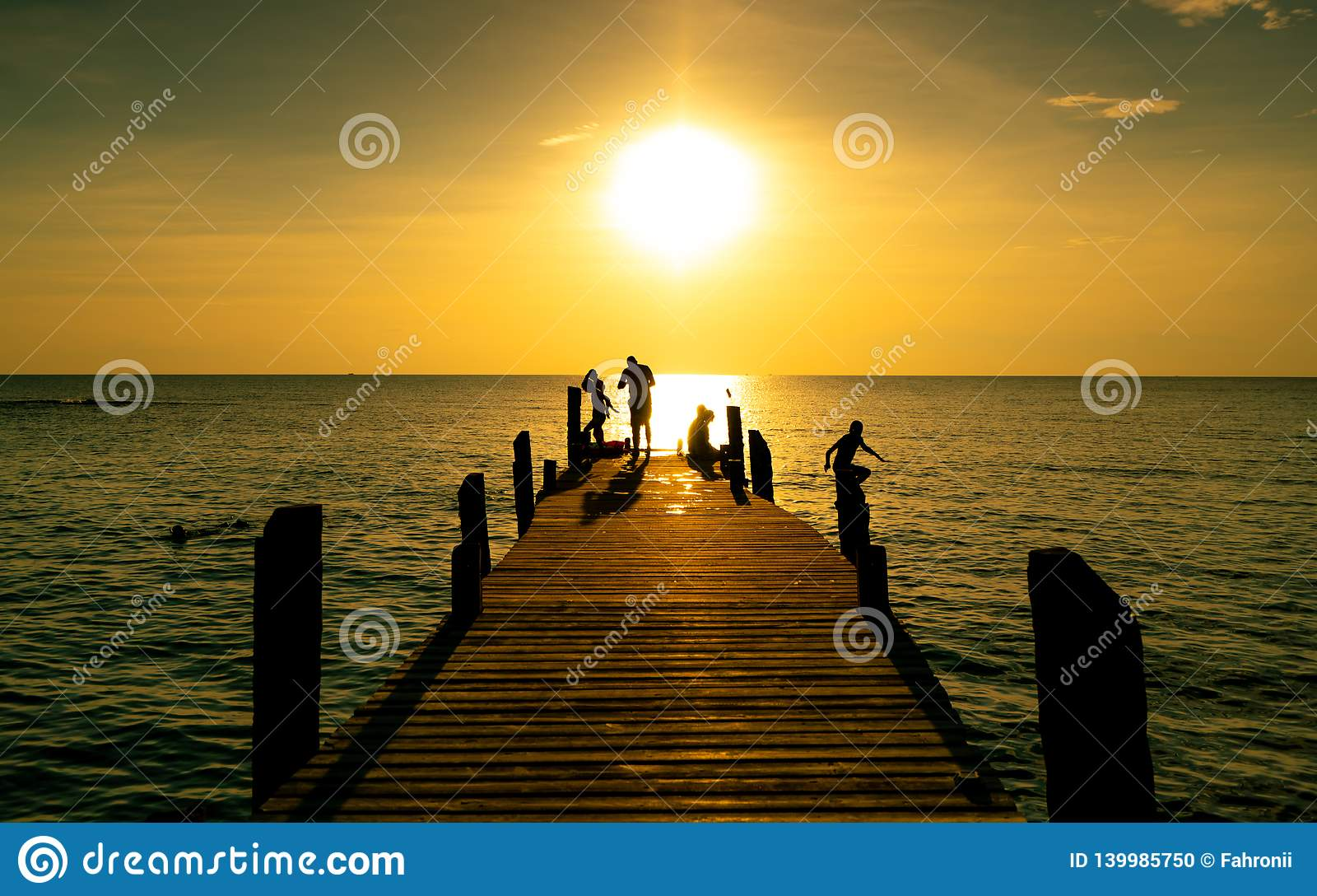 Lycklig familjlek tillsammans på sommarsemester på träbron på solnedgången Förälder och barn som spelar på stranden på ferie
