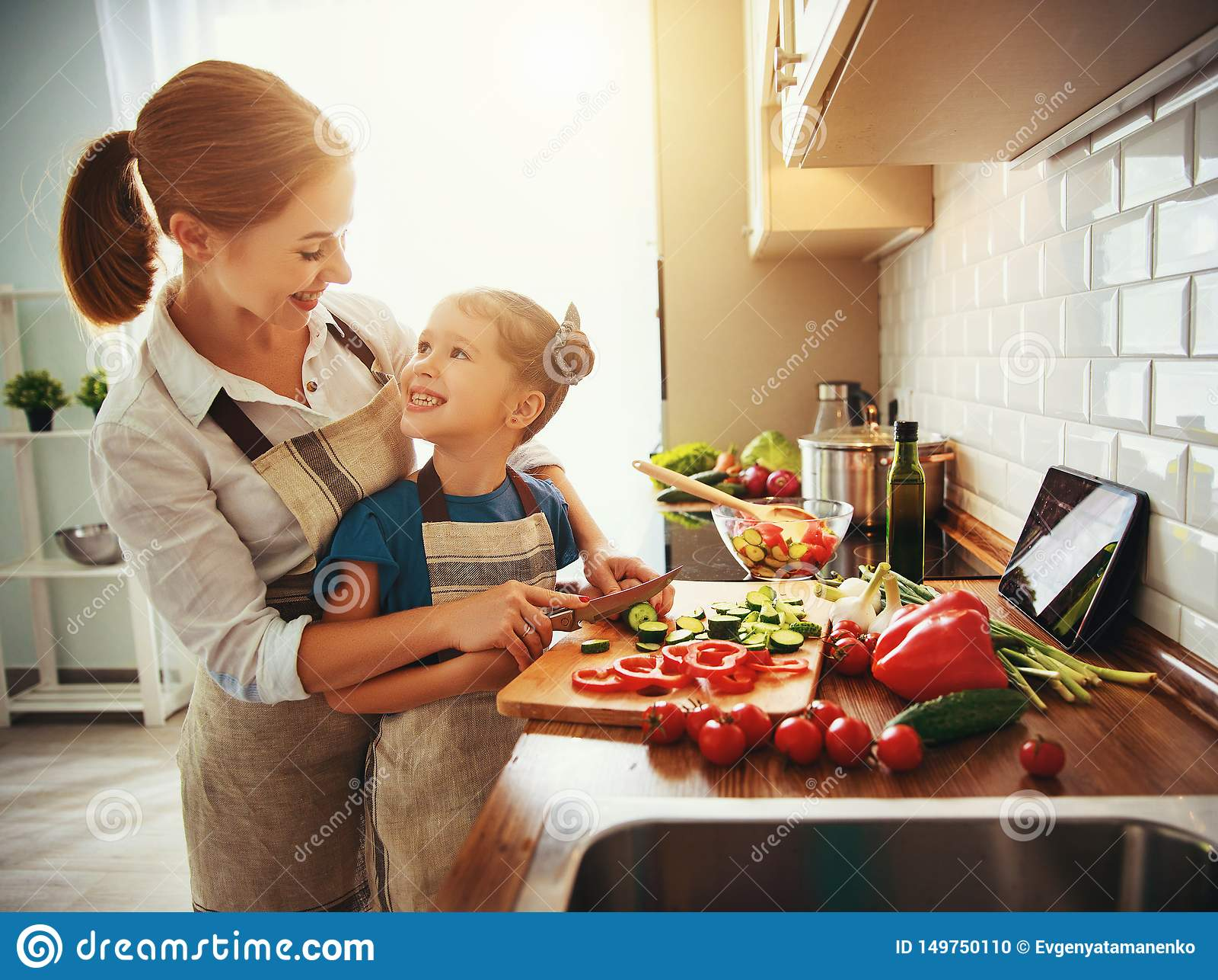 Lycklig familjmoder med barnflickan som f?rbereder gr?nsaksallad