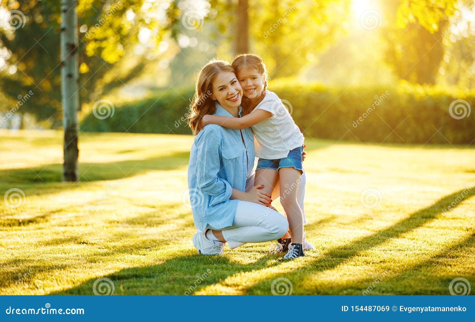 Lycklig familjmoder och barndotter i natur i sommar