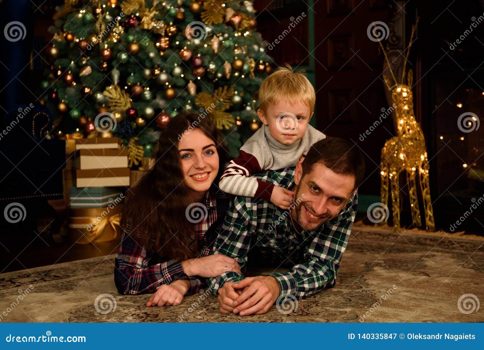 Lycklig familjmoderfader och att behandla som ett barn nära julträd hemma