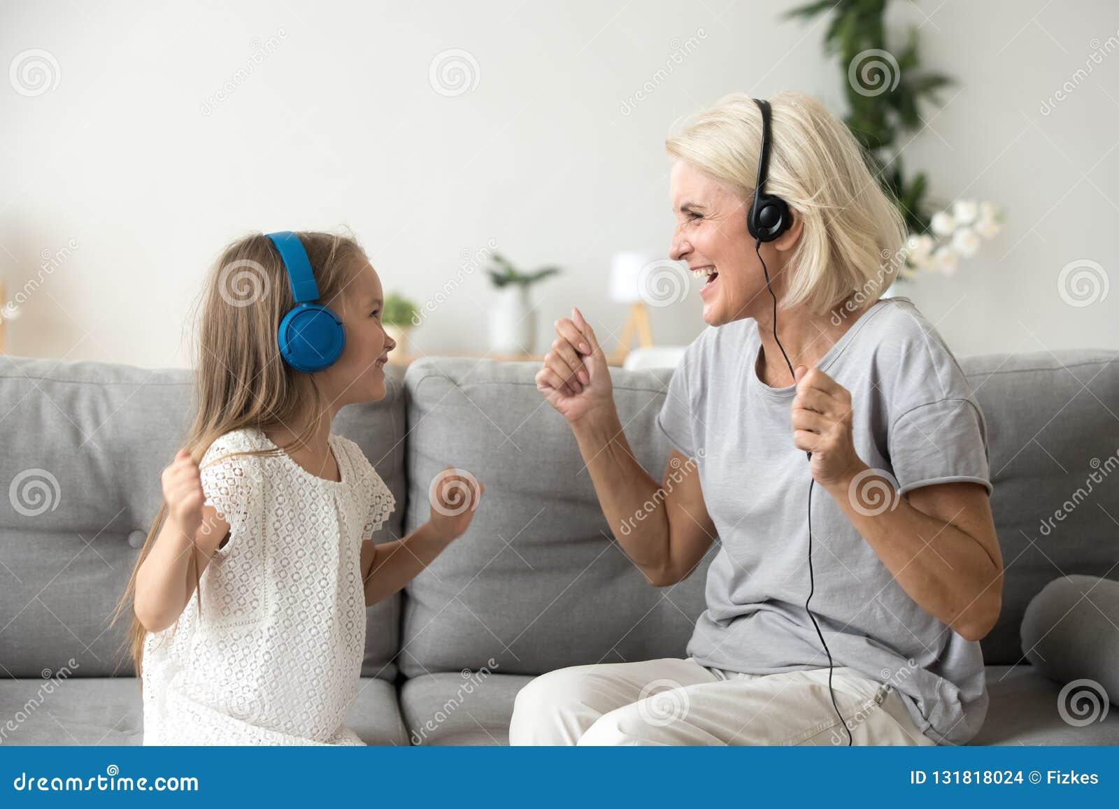 Lycklig farmor och sondotter som lyssnar till musik i headph