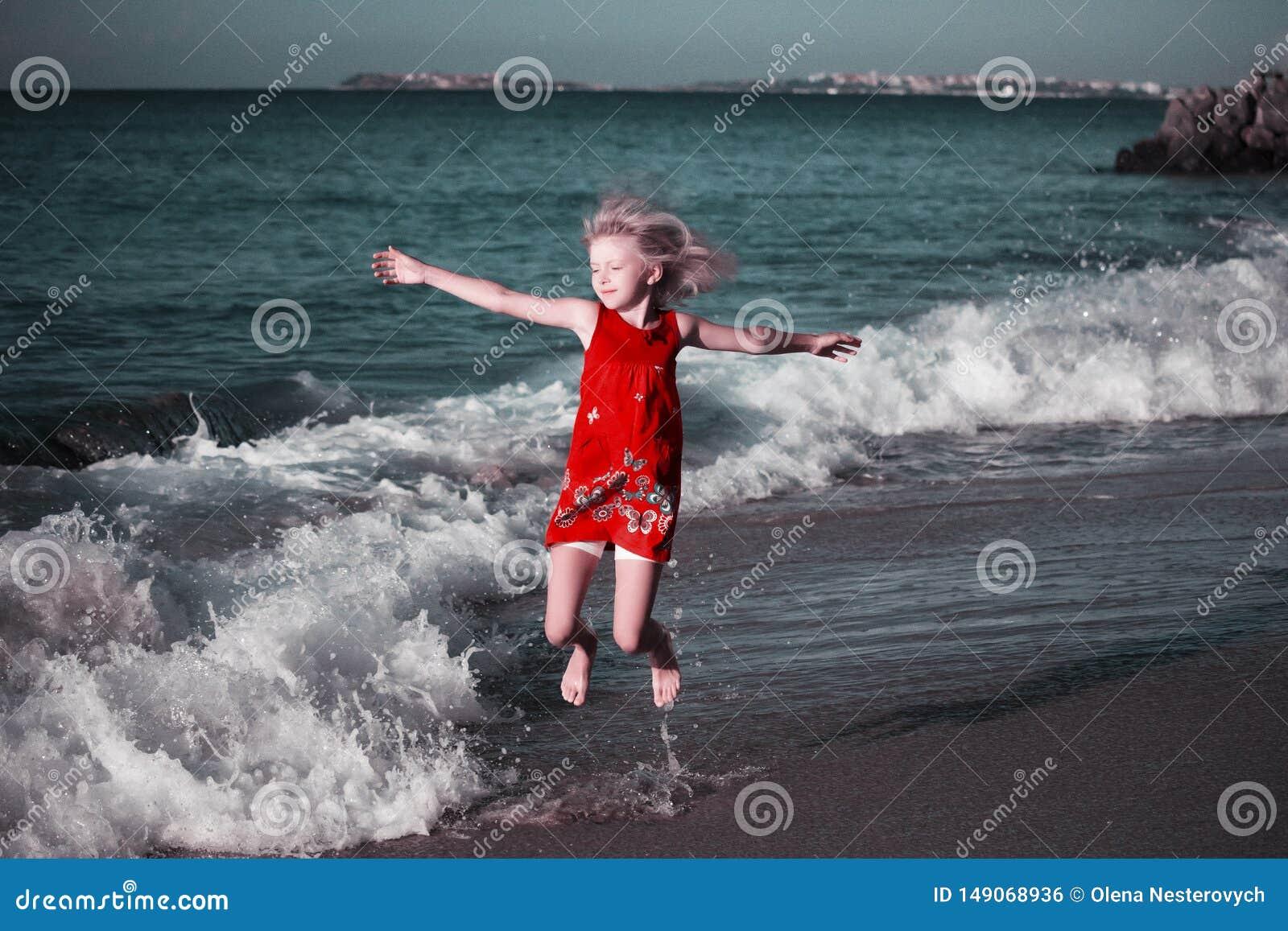 Lycklig flicka i kul?r kl?nning som hoppar p? v?gorna p? stranden