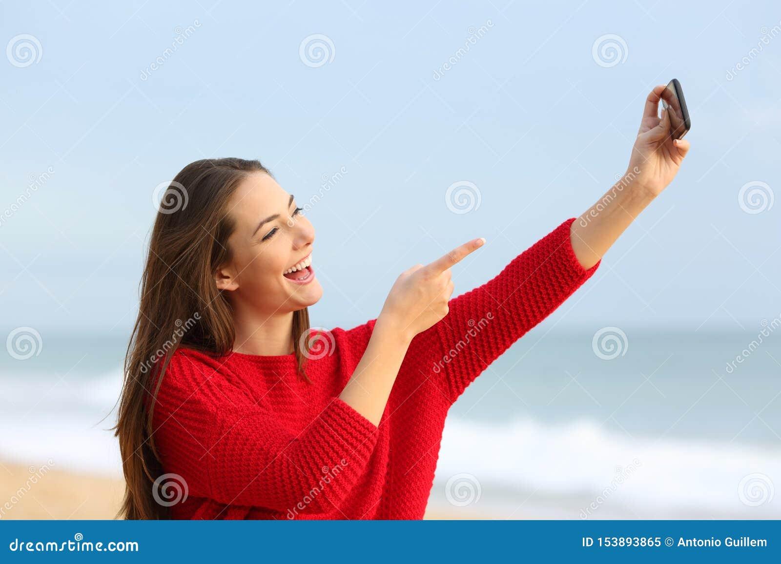 Lycklig flicka i röda tagande selfies på stranden