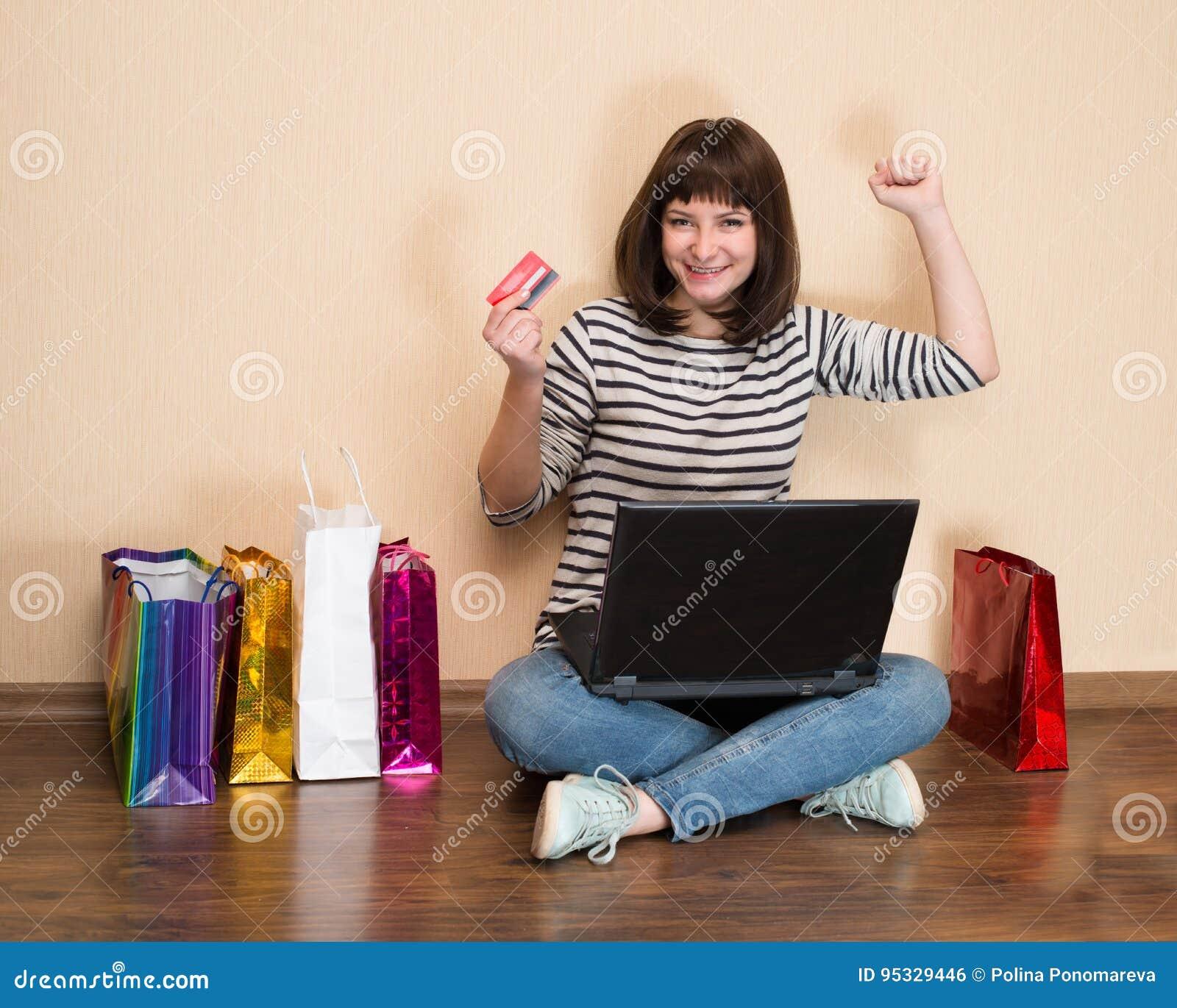 Lycklig flicka med shoppingpåsar som sitter på golvet med bärbar dator a