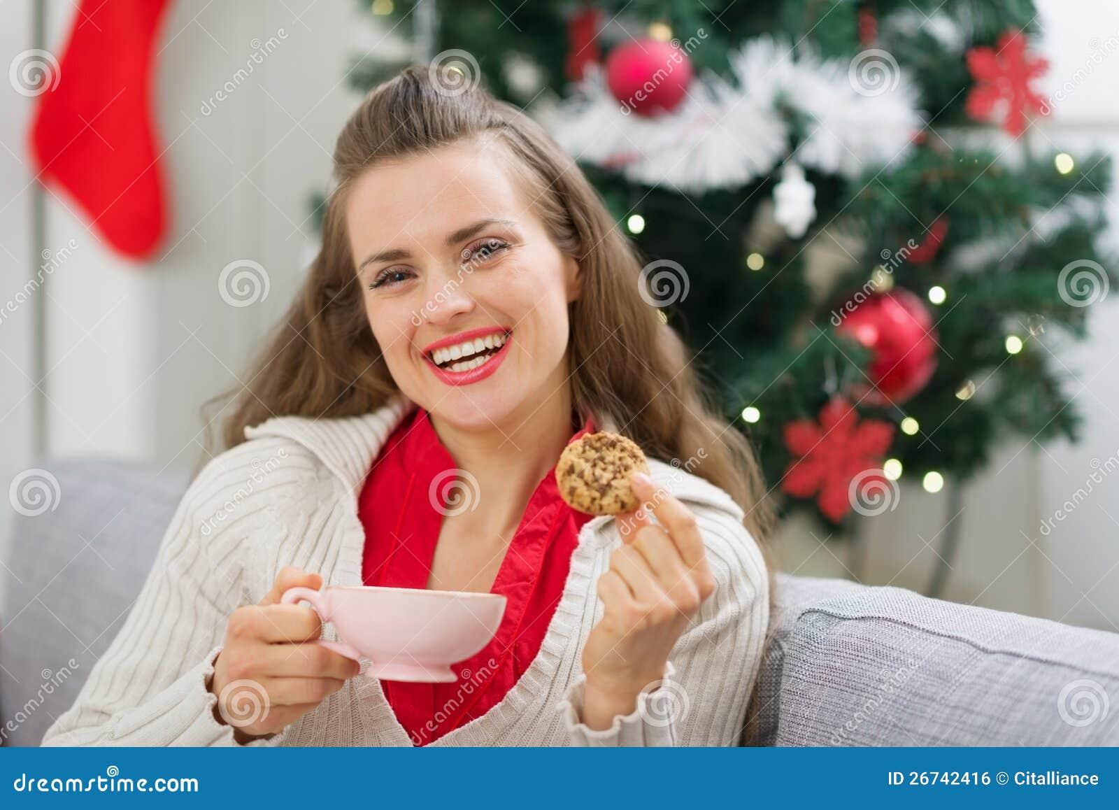 Lycklig flicka nära julgran med koppen och kakan