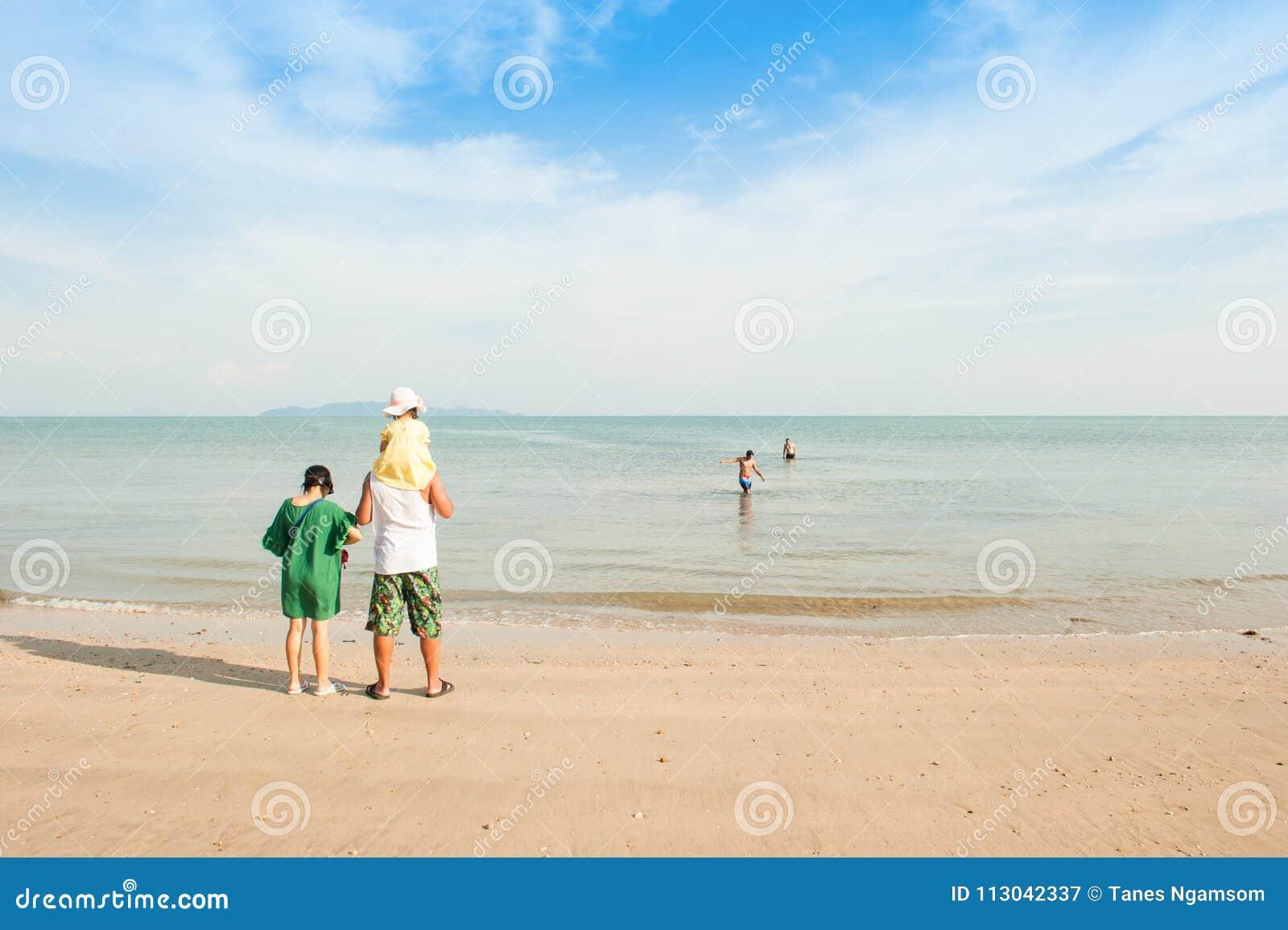 Lycklig flicka och familj på stranden