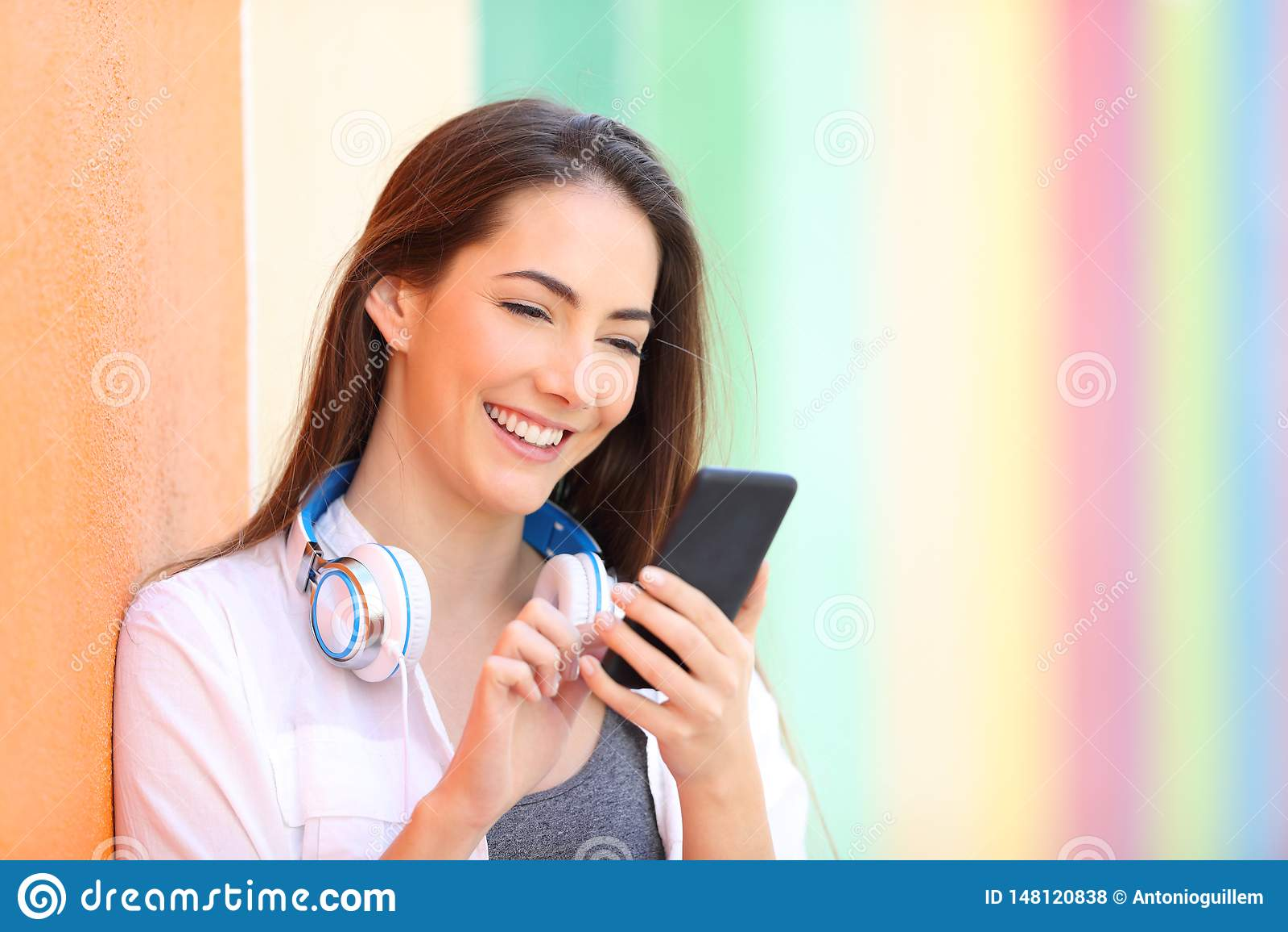 Lycklig flicka på en färgrik vägg som kontrollerar telefoninnehållet