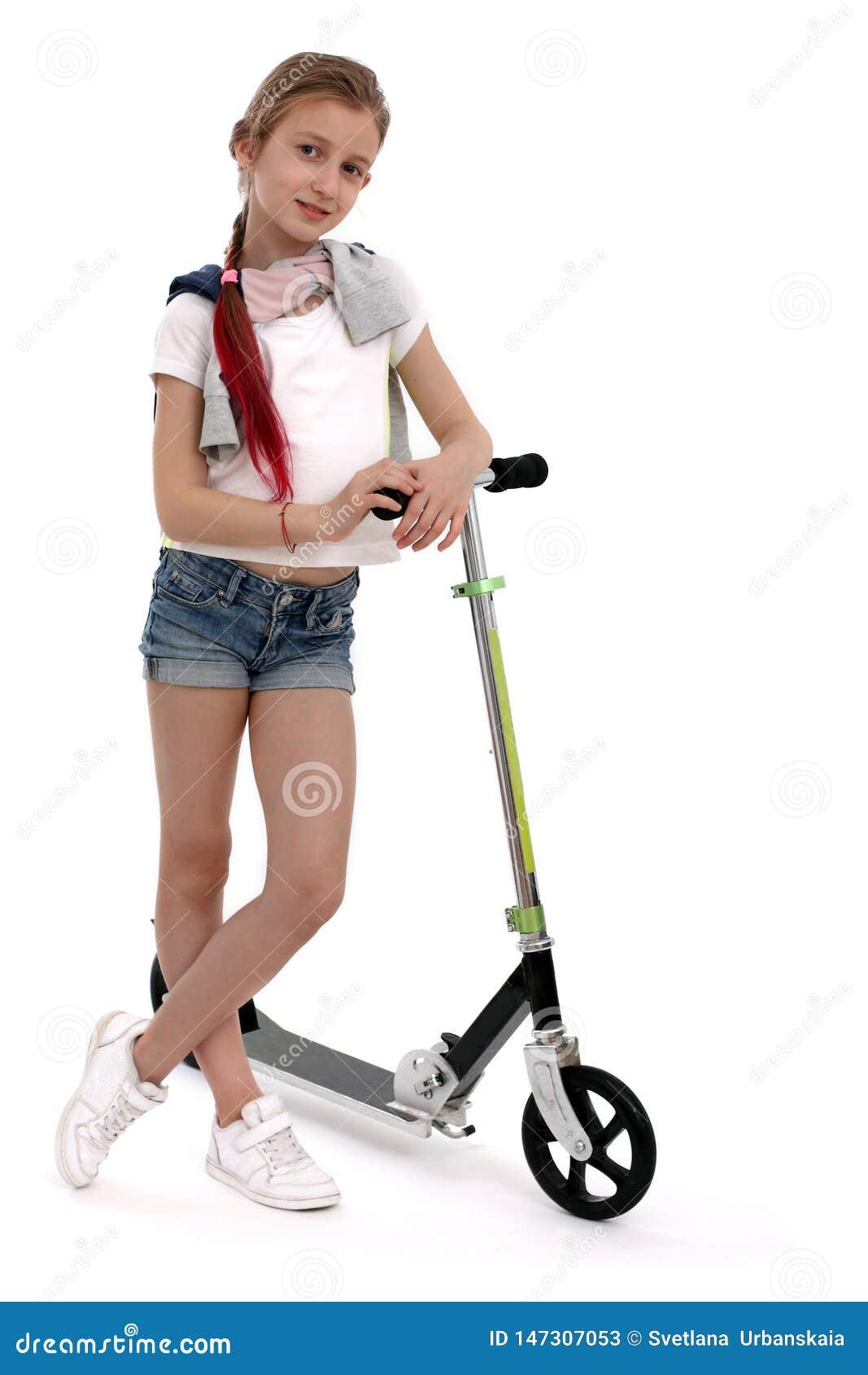 Lycklig flicka på sparkcykeln som isoleras på vit