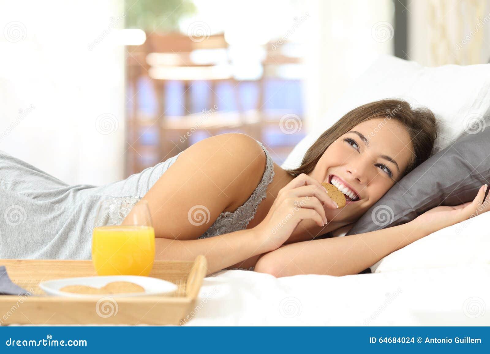 Lycklig flicka som äter dietiska kakor på frukosten