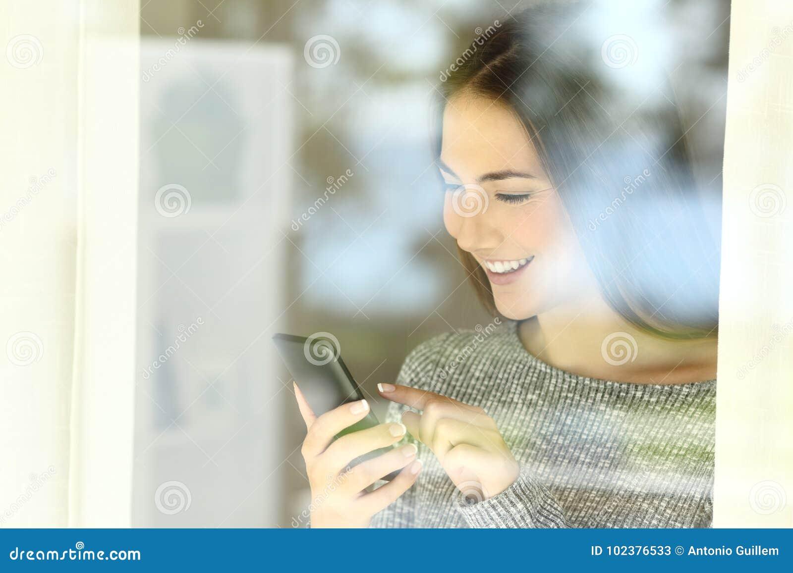 Lycklig flicka som kontrollerar det smarta telefoninnehållet på linje
