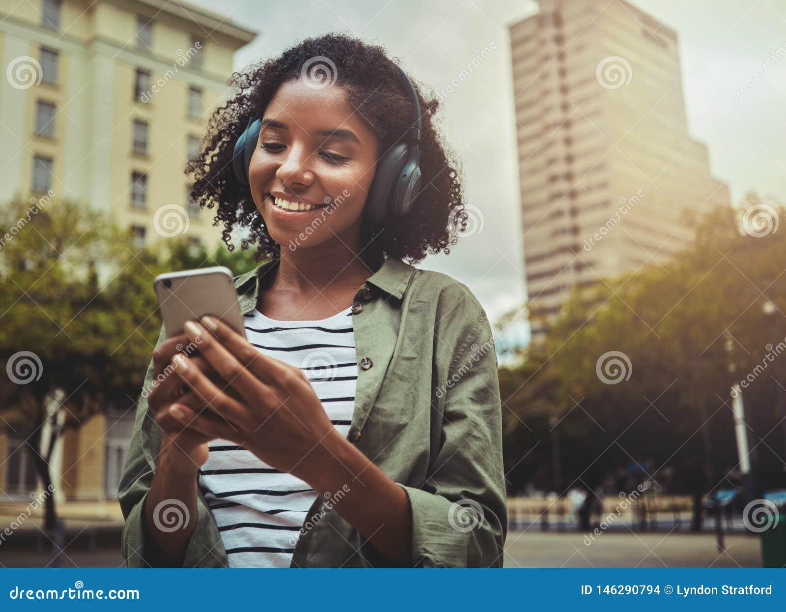 Lycklig flicka som lyssnar till musik som bläddrar det smarta telefoninnehållet
