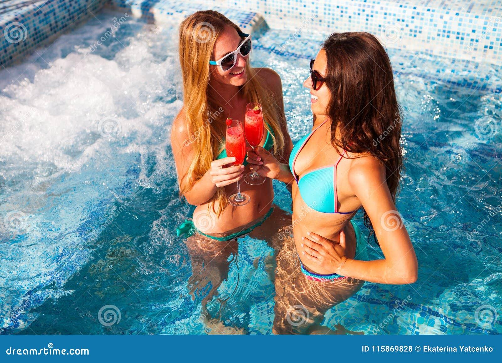 Lycklig flickvän med en drink på ett sommarparti vid pölen