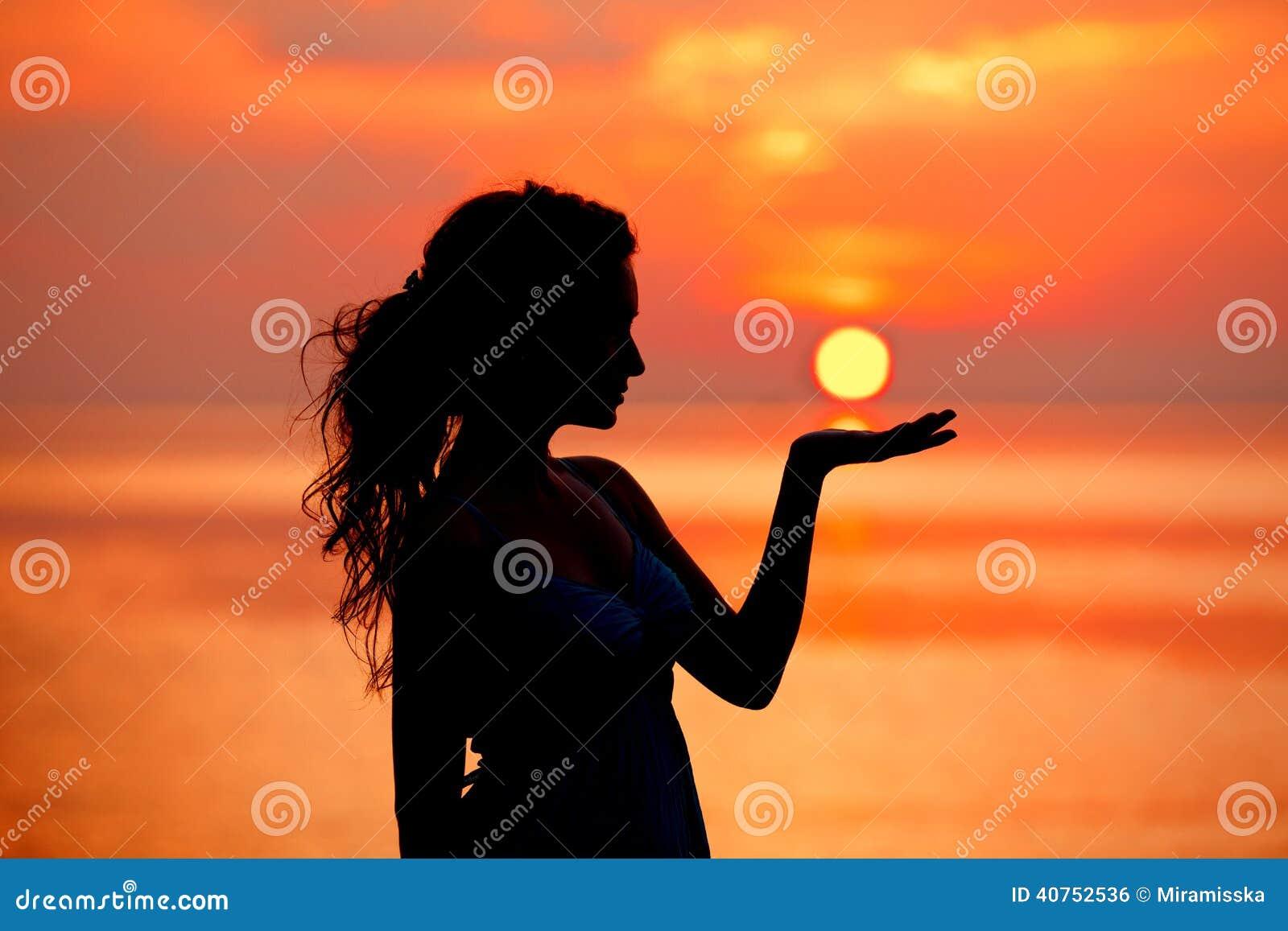 Lycklig fri kvinna som tycker om i havssolnedgång Silhouetted mot