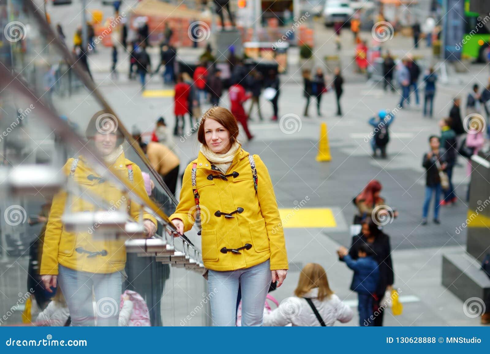 Lycklig fyrkant för sight för ung kvinna turist- tidvis i New York City Kvinnlig handelsresande som tycker om sikt av i stadens c