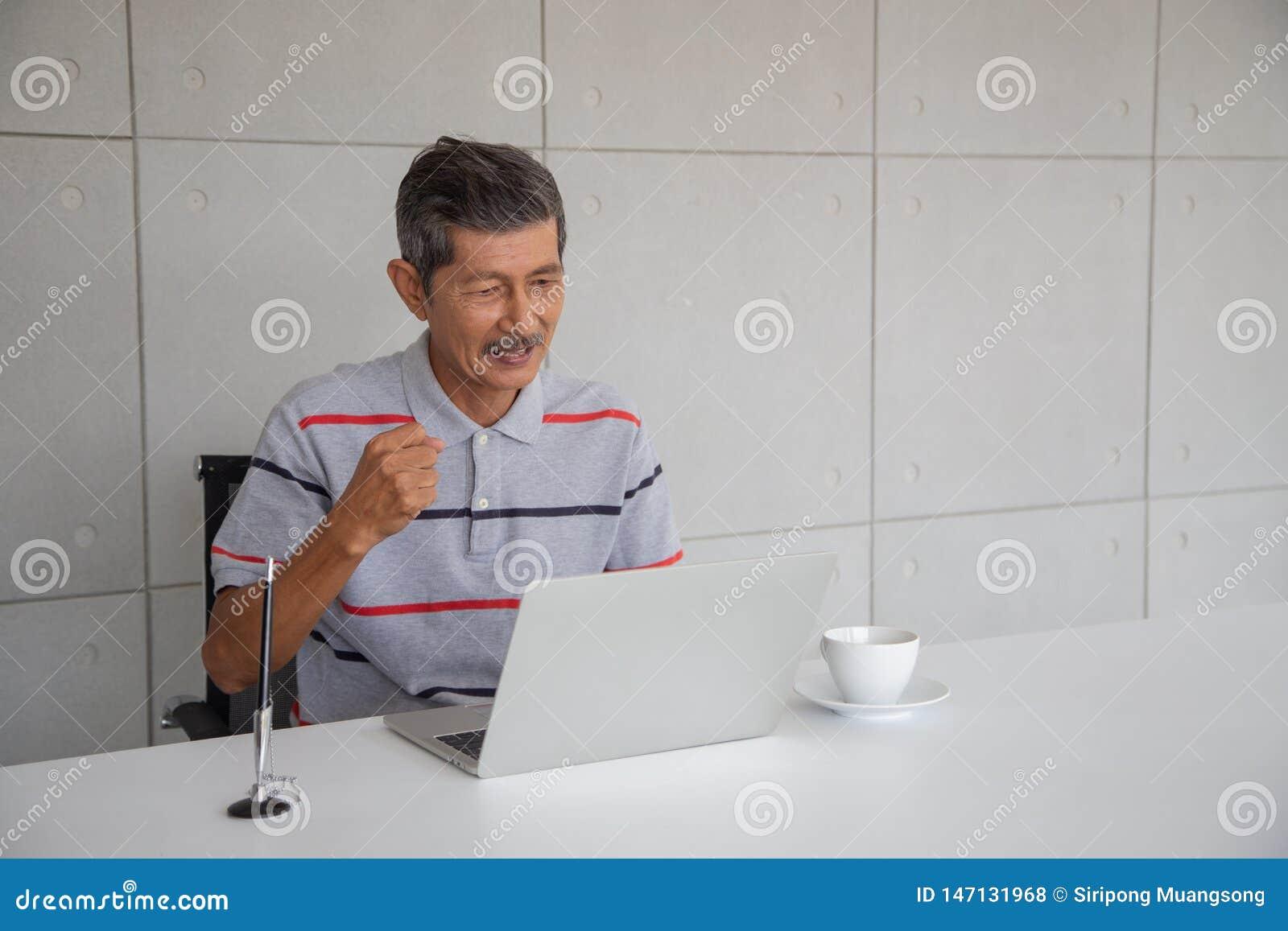 Lycklig gammal asiatisk man och leende med hans framg?ng