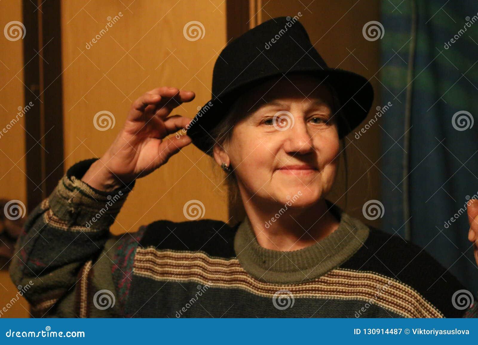 Lycklig gammal dam i svart hatt i skymning