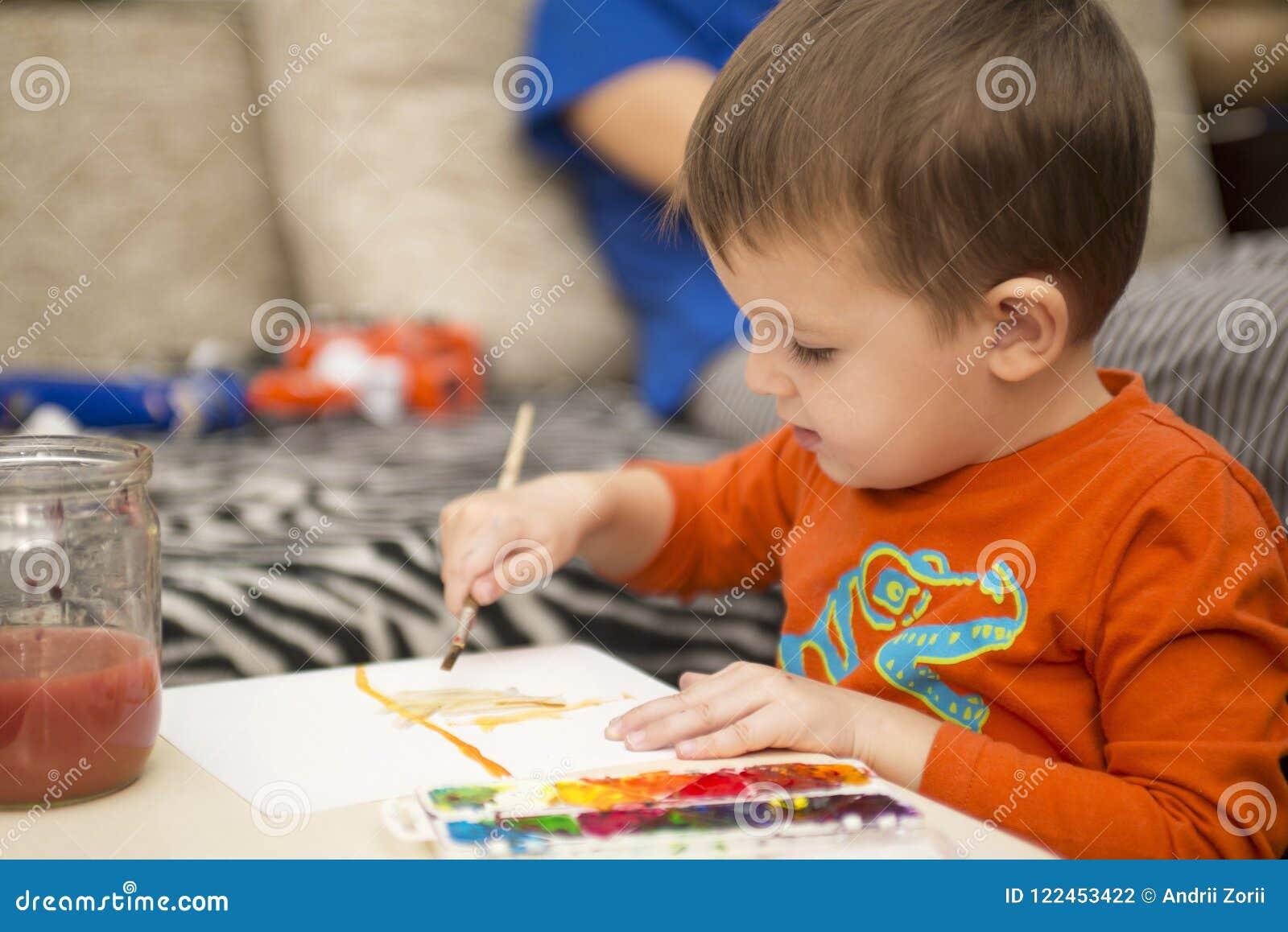 Lycklig gladlynt barnteckning med borsten genom att använda hjälpmedel för en målning lego för hand för byggnadsbegreppskreativit
