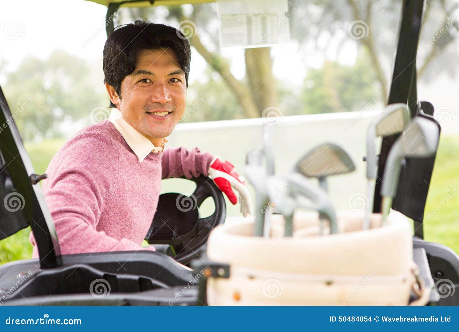 Lycklig golfare som kör hans golfbarnvagn som ler på kameran