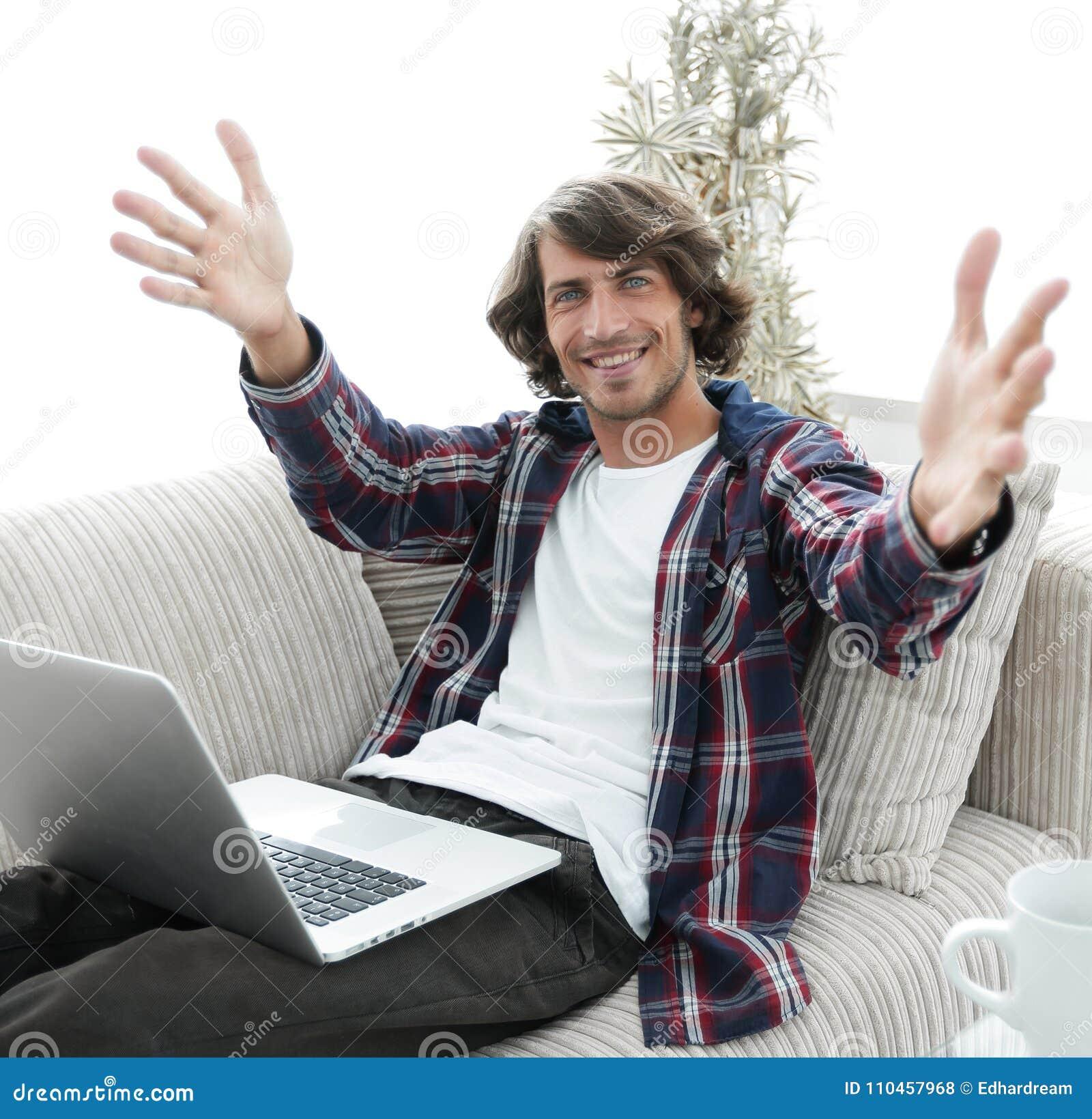 Lycklig grabb med ett bärbar datorsammanträde på soffan och hälsning med utsträckta händer