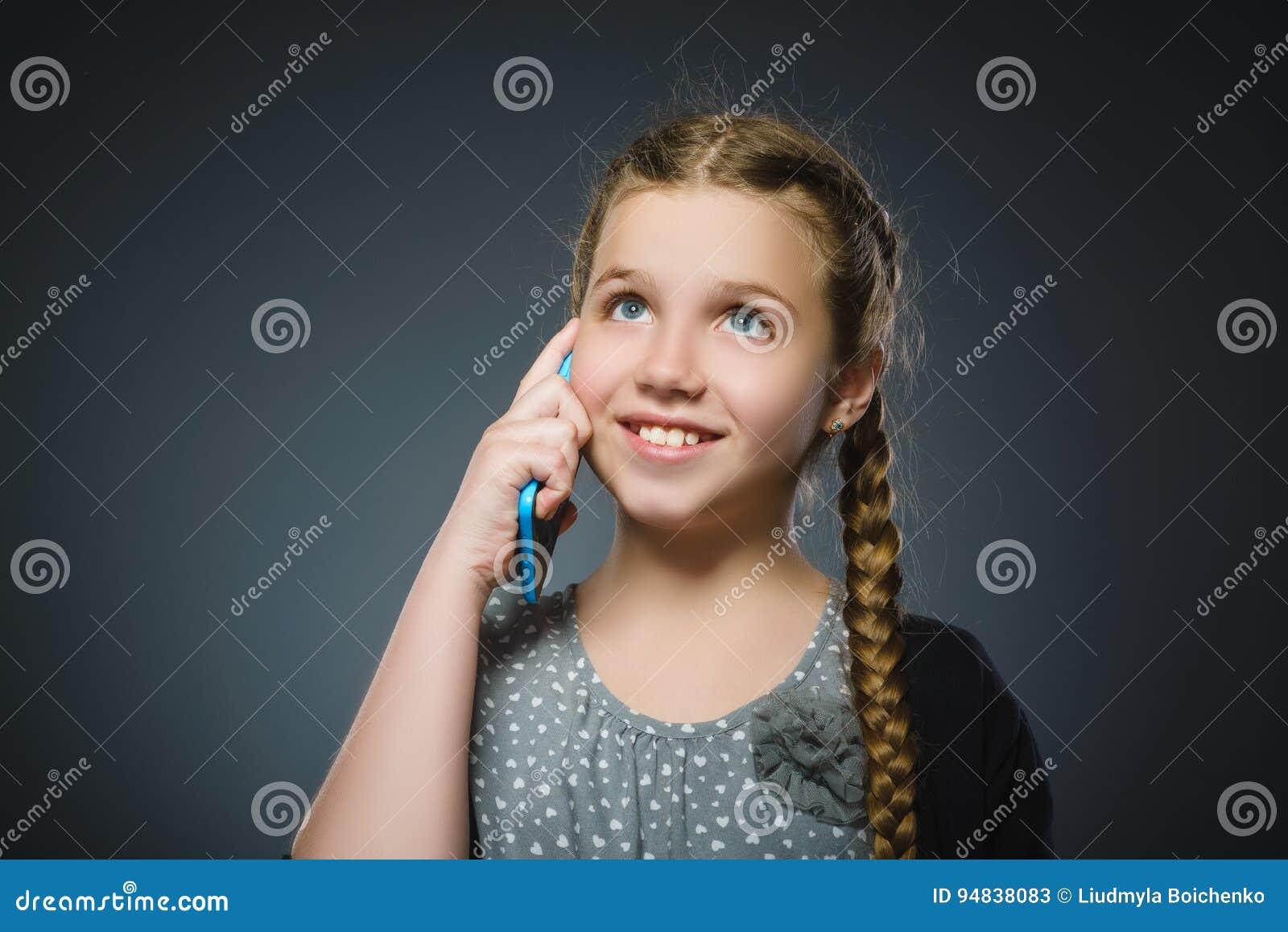 Lycklig gullig flicka med mobiltelefonen Isolerat på grå färg