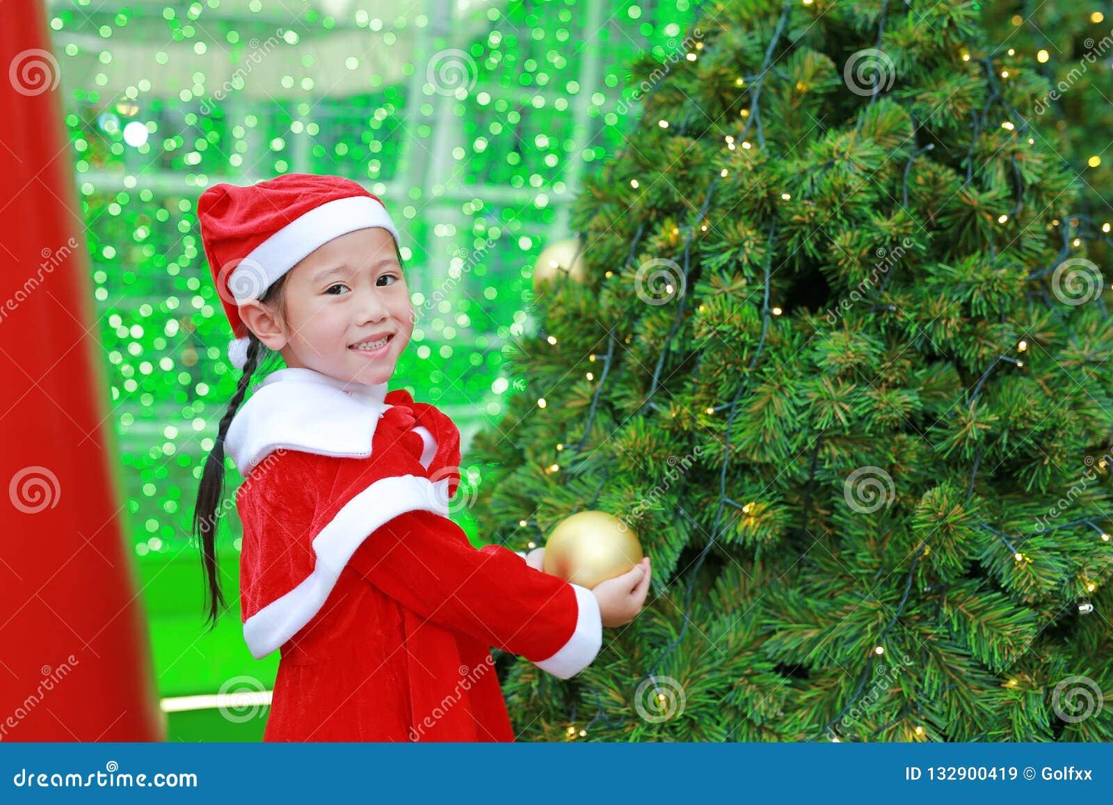 Lycklig gullig liten asiatisk barnflicka i jultomtendräkt nära julgranen och bakgrund Begrepp för julvinterferie